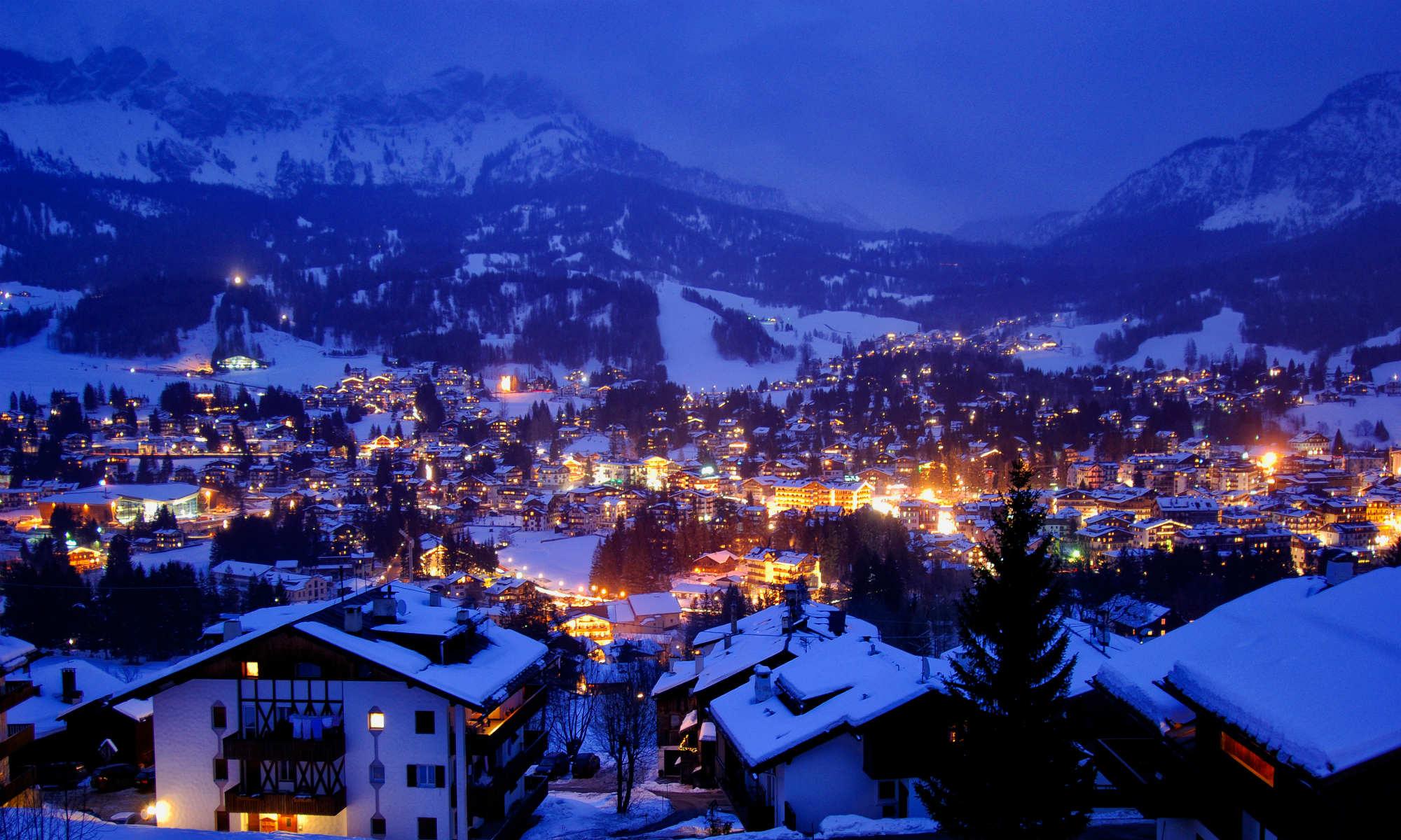Vista notturna sulla città innevata di Cortina d'Ampezzo, illuminata dalle luci provenienti dalle finestre delle abitazioni e dai locali aperti.