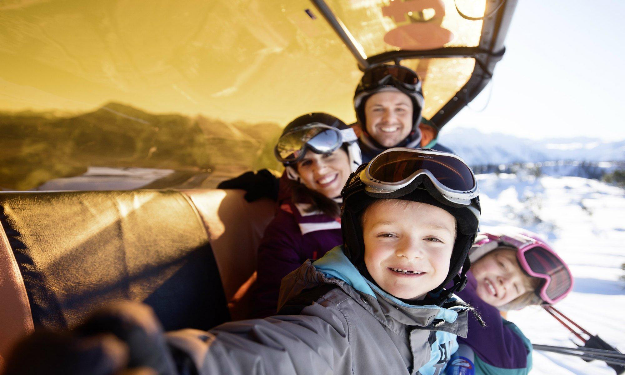 Een jongetje maakt een selfie in de skilift met zijn ouders en zus.