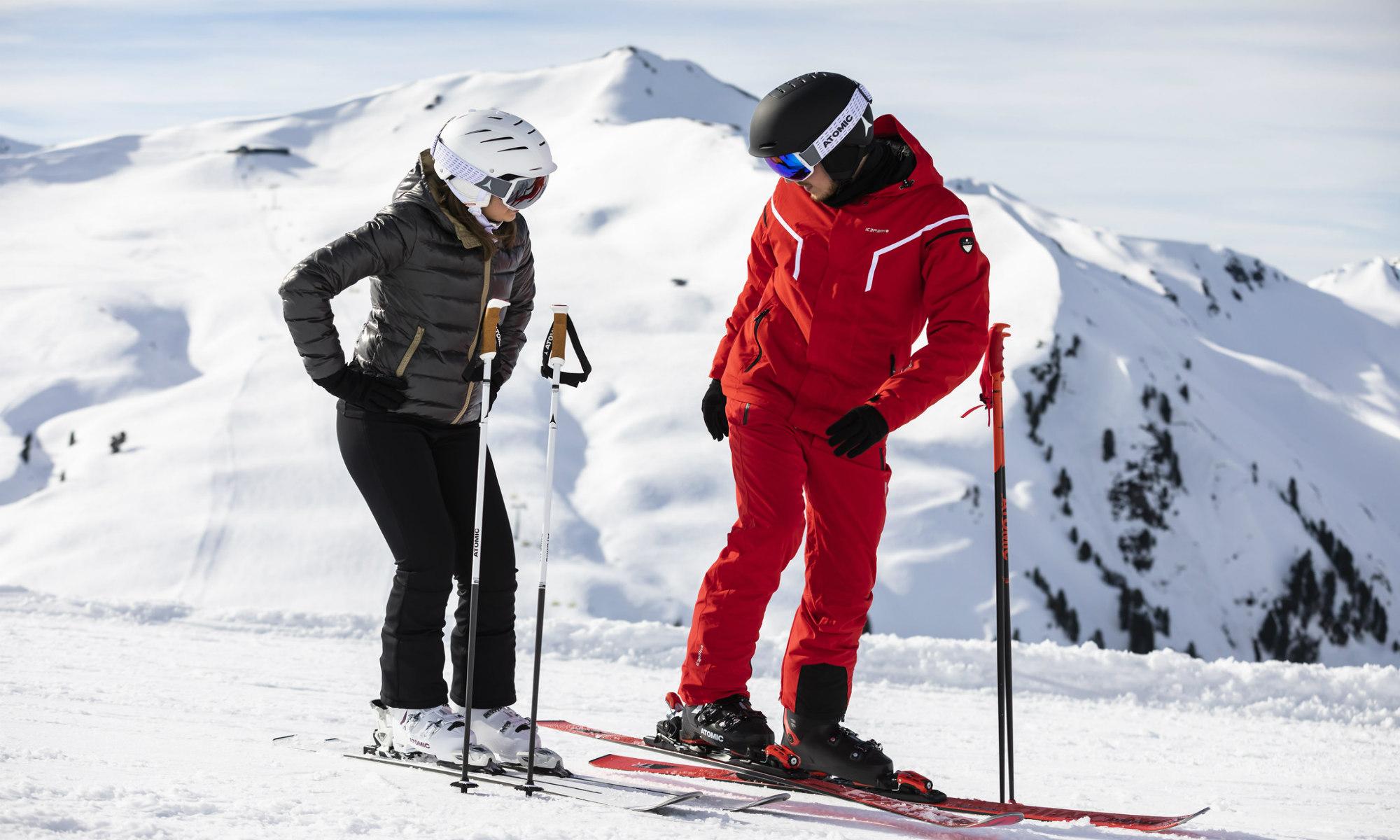 Een privéleraar helpt zijn leerling met haar skitechniek.
