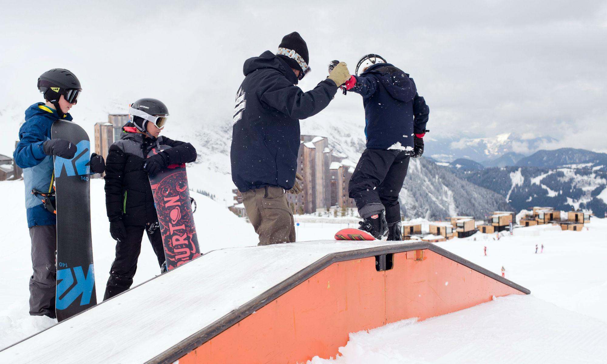 Un papa aide son fils à franchir un module dans le snowpark d'Avoriaz.