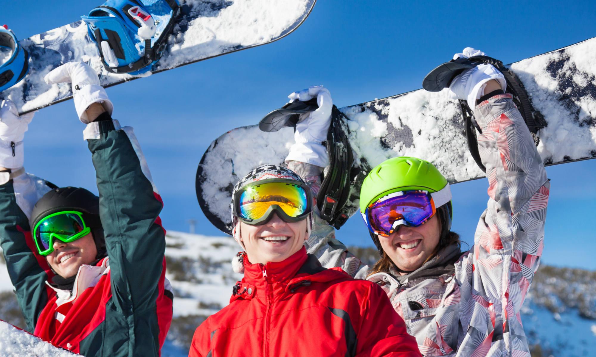 3 amis souriants avec leurs snowboards sur les pistes de Val Thorens.
