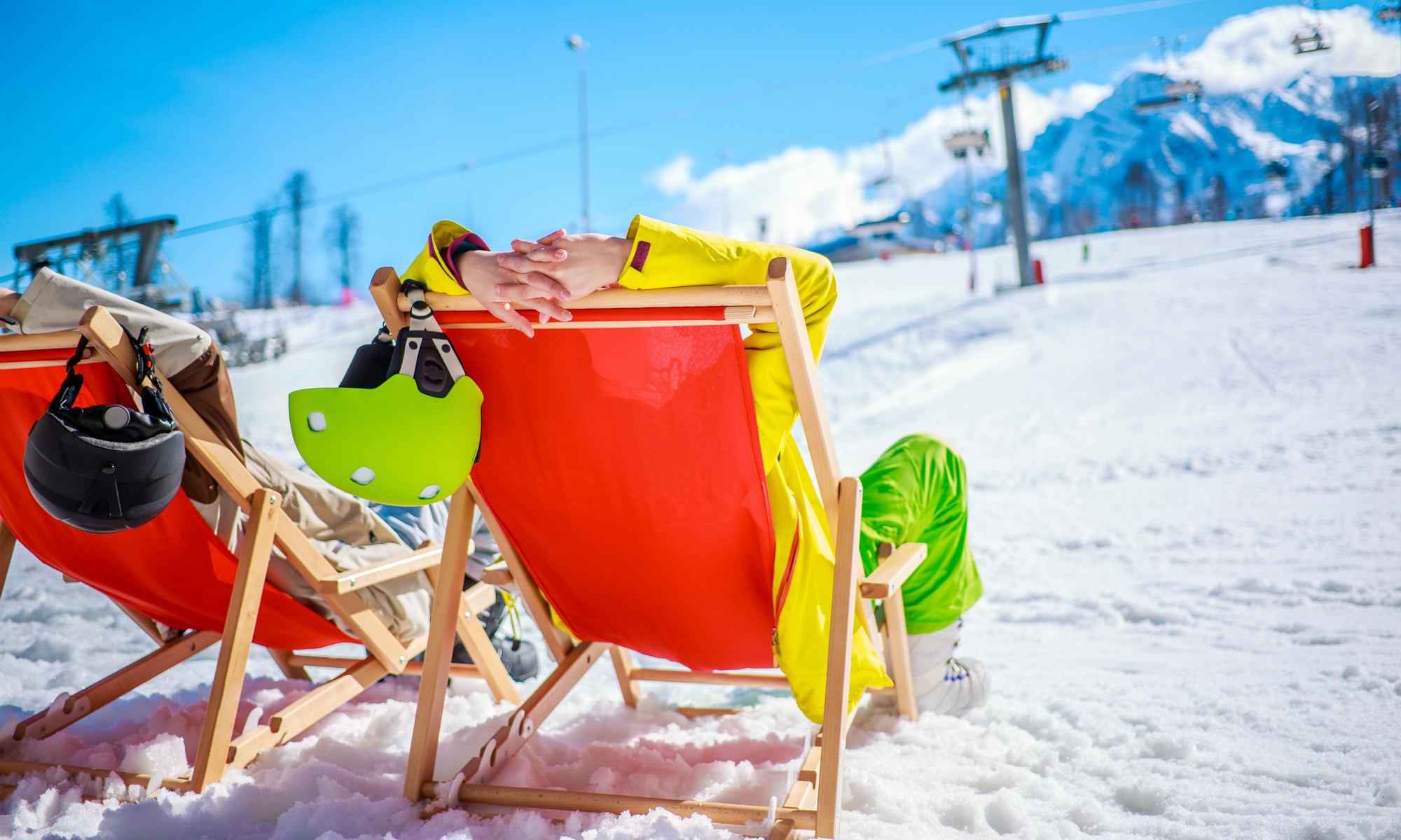 2 sciatori si rilassano a bordo pista su delle sdraio colorate a Cervinia.