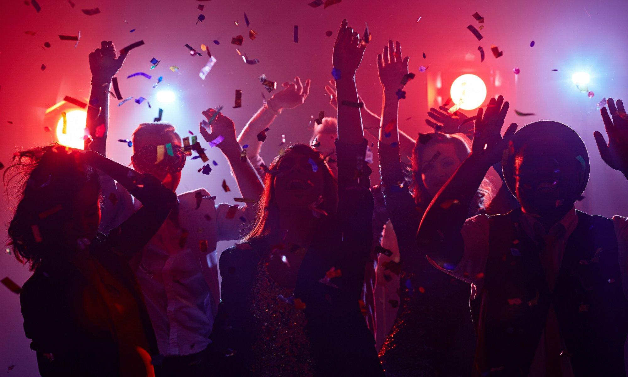 Un gruppo di amici balla in discoteca con luci soffuse e coriandoli colorati che volano per la sala.