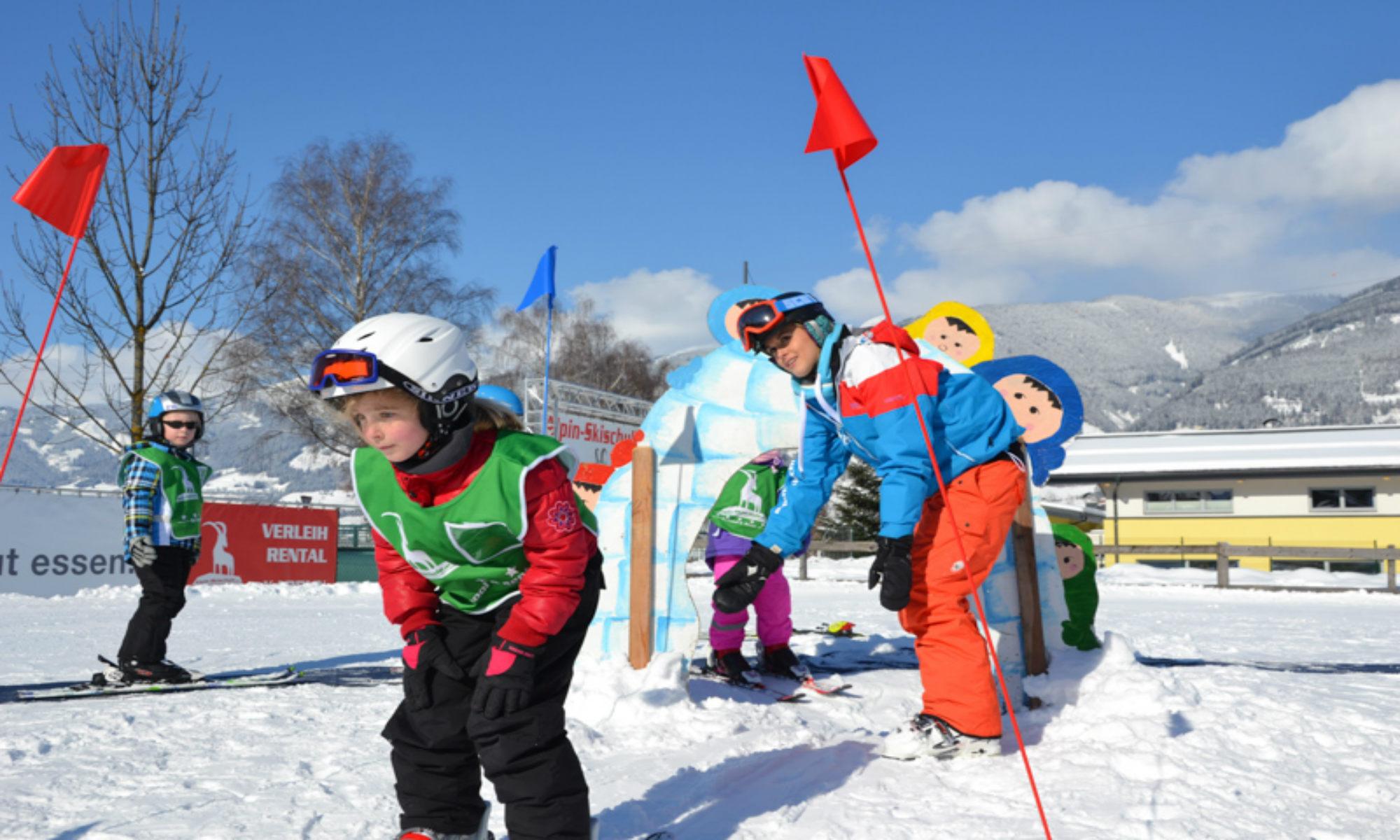 Een meisje is bezig met een ski-oefening onder het toeziend oog van haar skilerares.