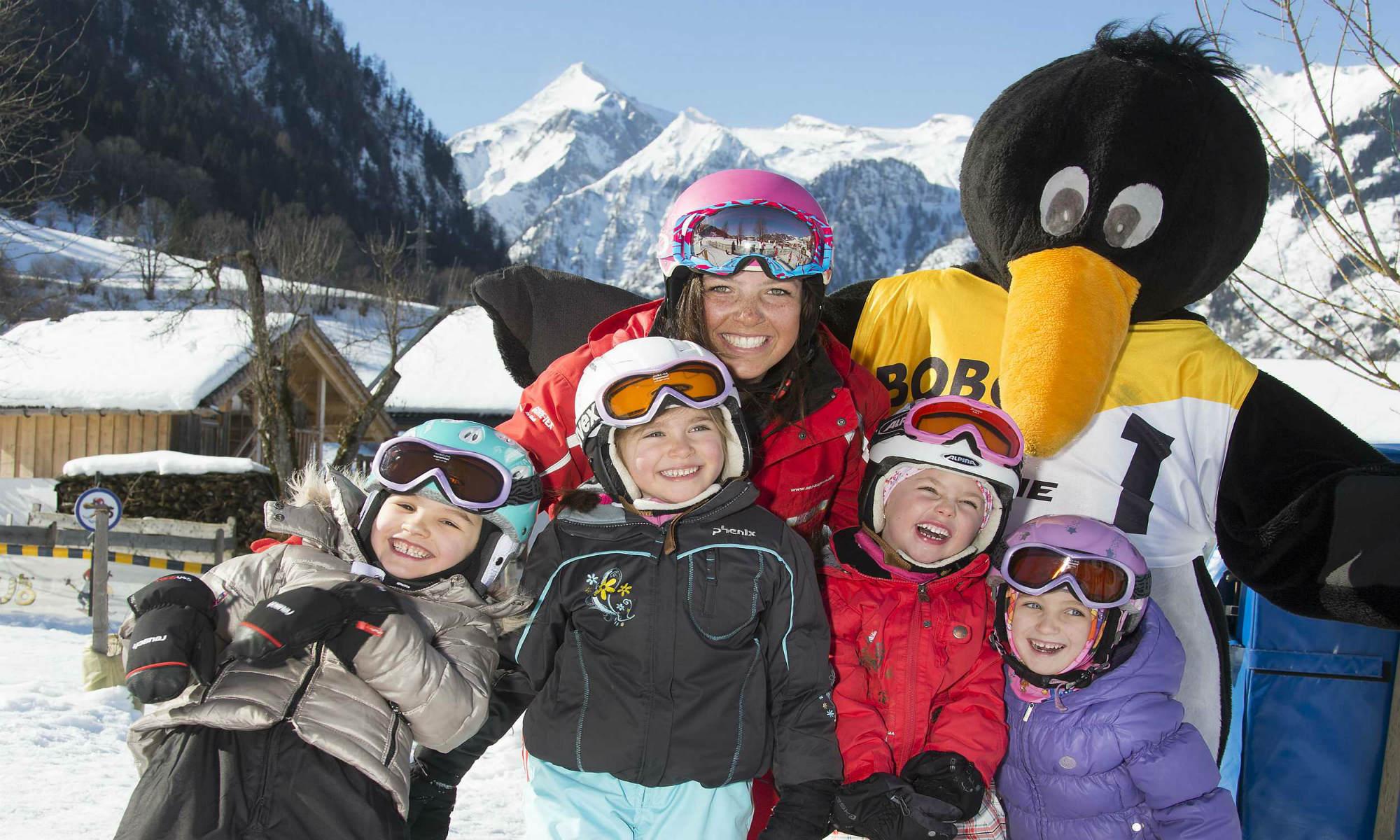 Vier meisjes hebben veel plezier met hun skilerares en Bobo de pinguïn.