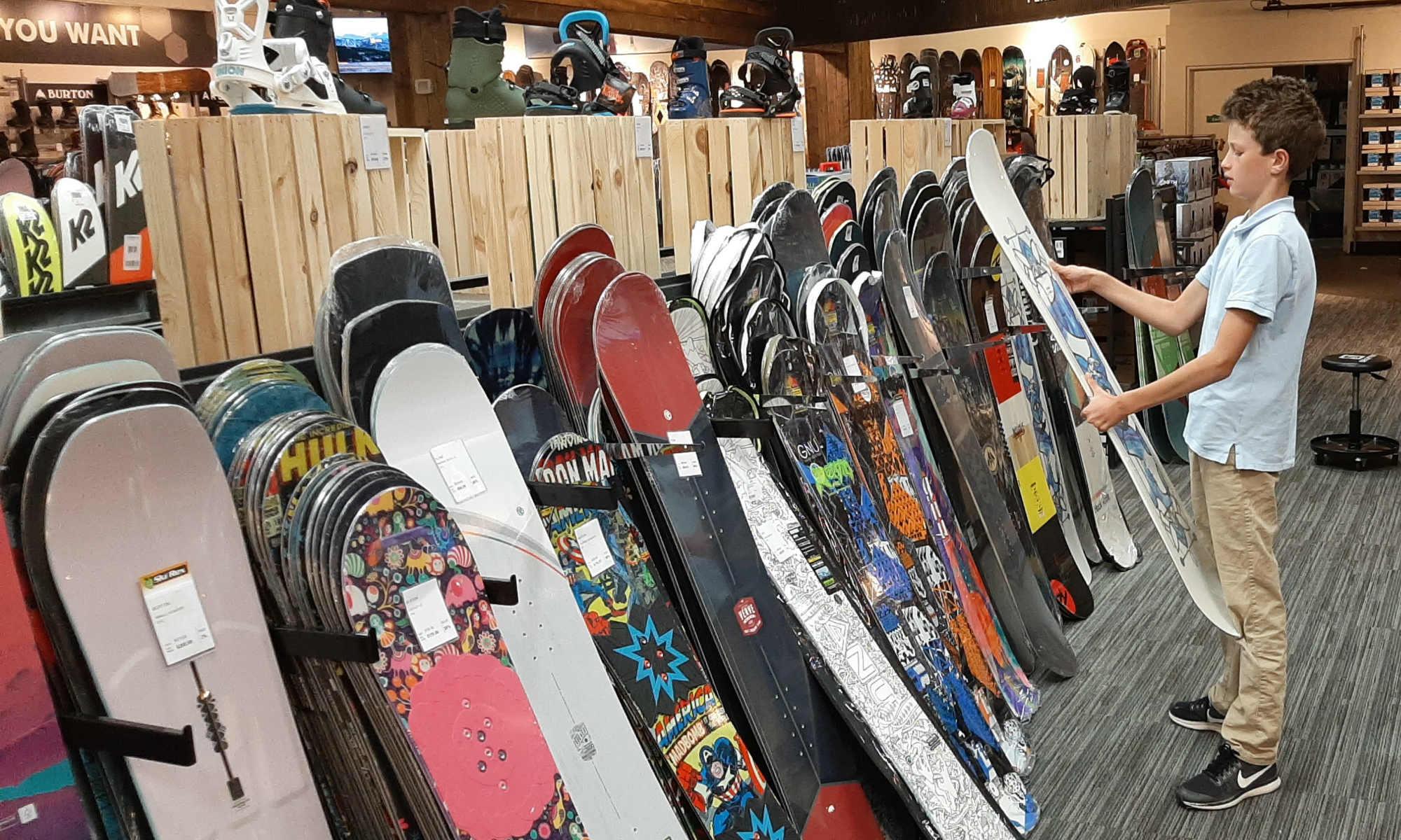 Un ragazzo sceglie la sua tavola da snowboard tra una vasta selezione.