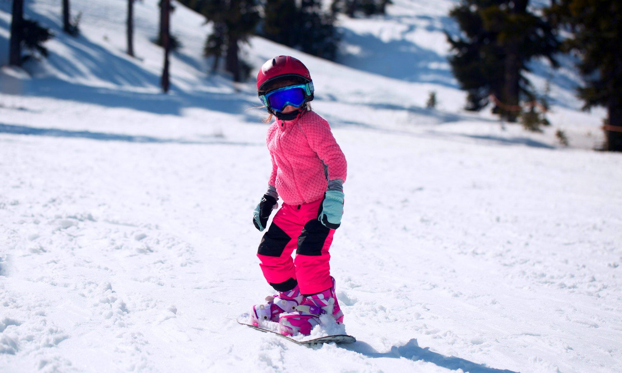 Una bambina scivola sulla sua tavola da snowboard lungo un pendio dolce.