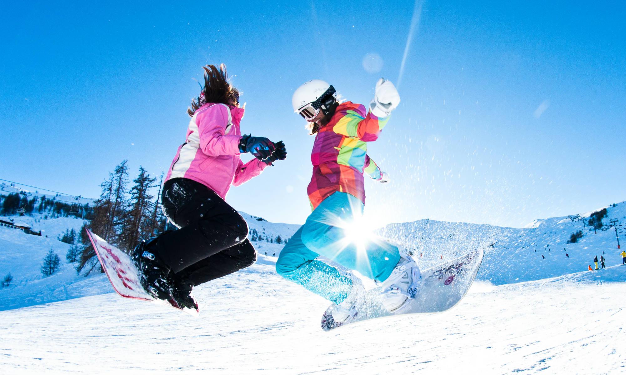 2 giovani sullo snowboard saltano assieme sulla neve.