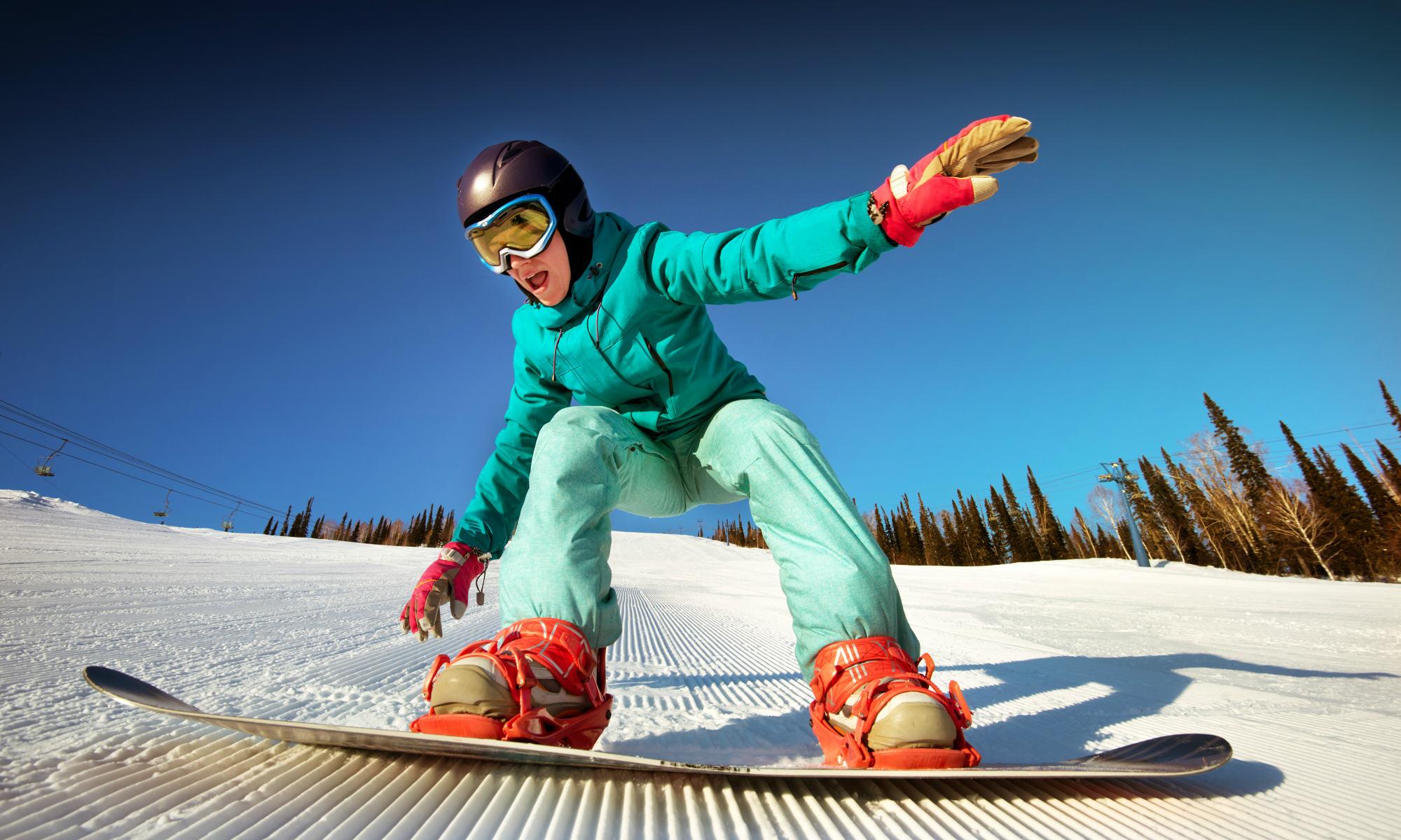 Una ragazza sullo snowboard in procinto di cadere sulla neve.