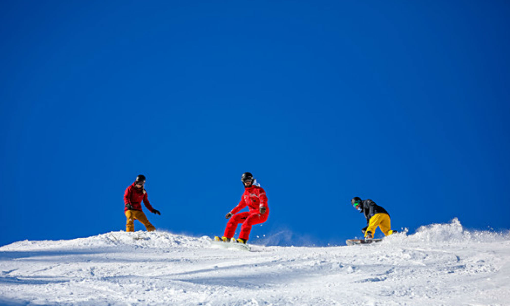 Deux snowboarders et leur moniteur travaillent leurs virages sur les pistes ensoleillées de l'Alpe d'Huez.