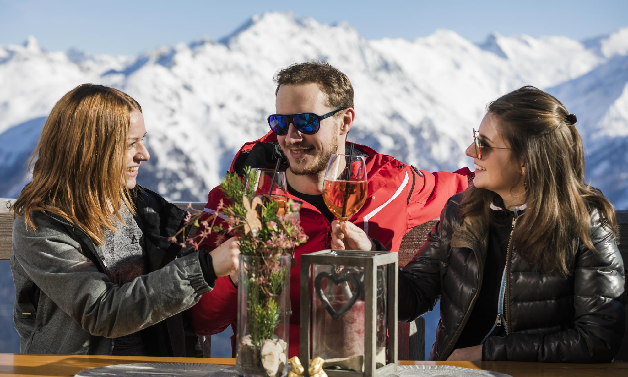 3 amici brindano felici di fronte a una montagna innevata.