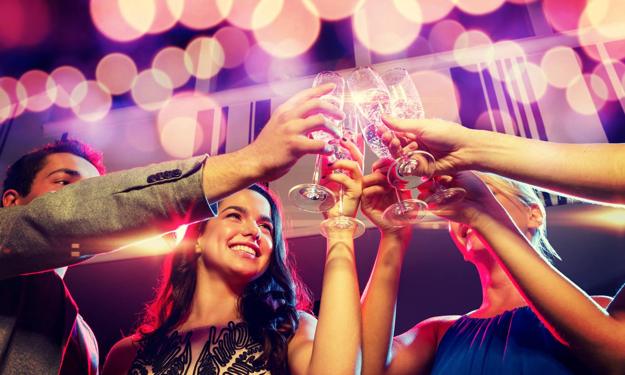 4 amici vestiti eleganti brindano con calici di champagne a Cortina D'Ampezzo.