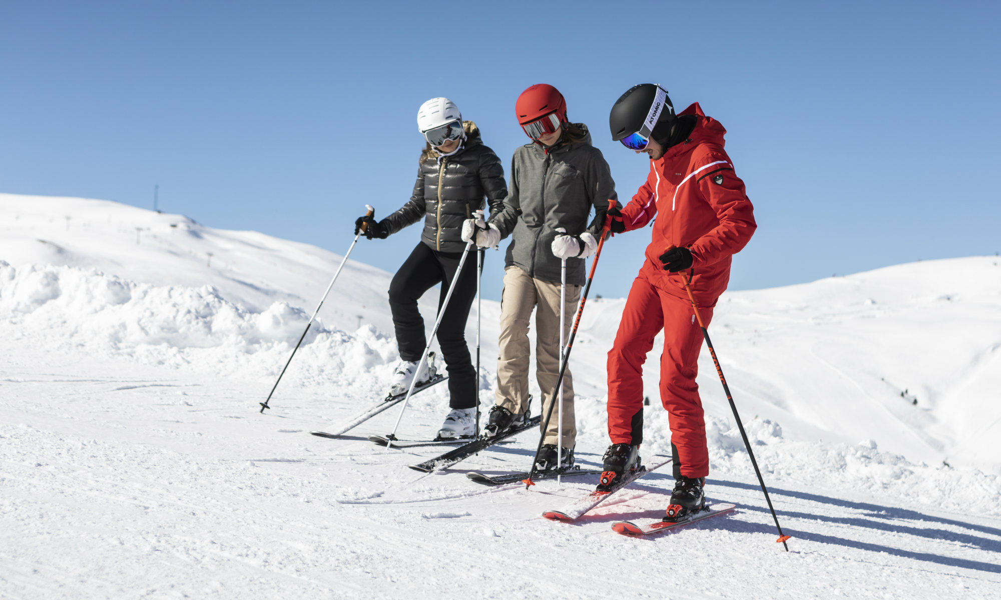 Un maestro di sci insegna a due allievi come posizionare gli sci sulle piste di Madonna di Campiglio.