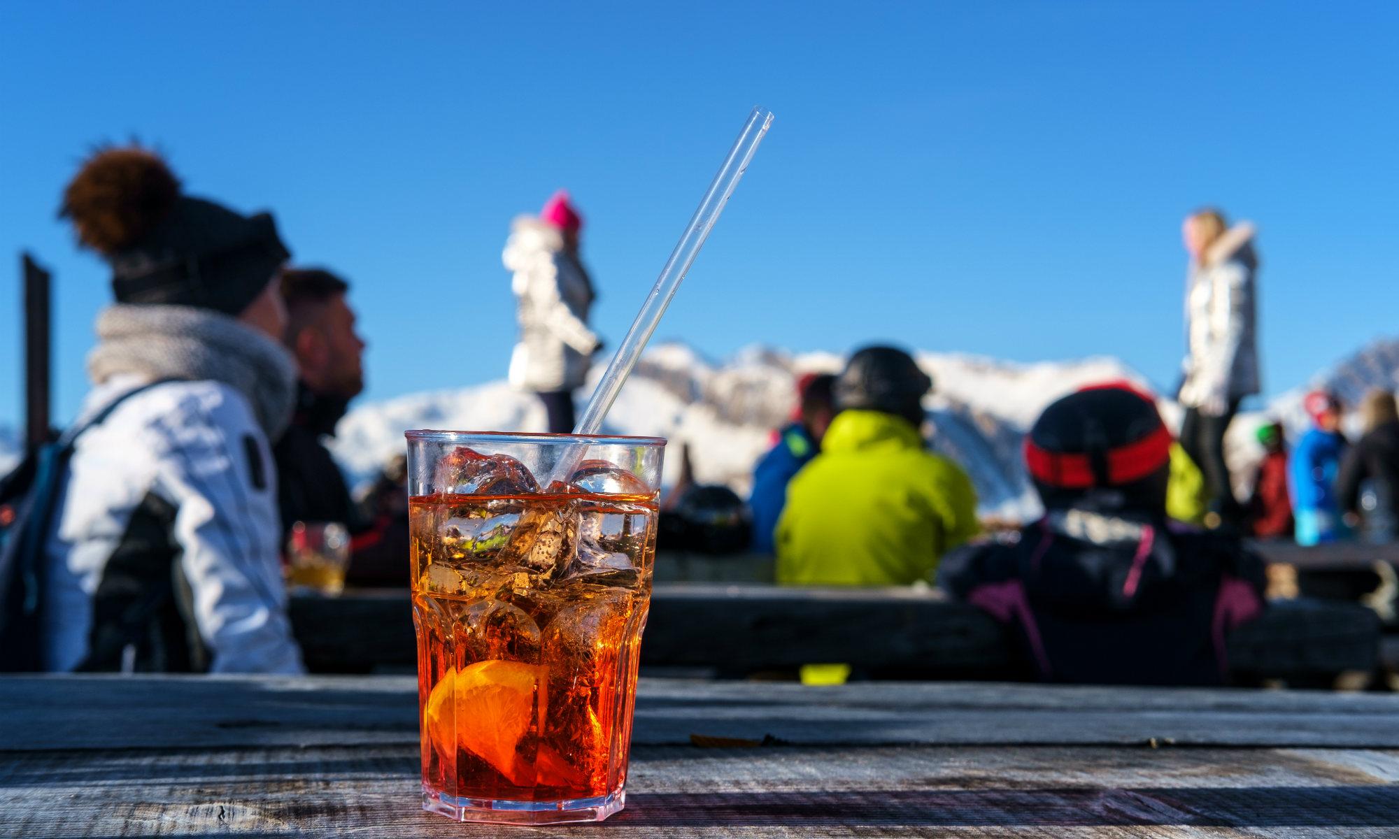 Un cocktail posizionato in primo piano e sullo sfondo sciatori seduti che si godono l'aperitivo a Sestriere.
