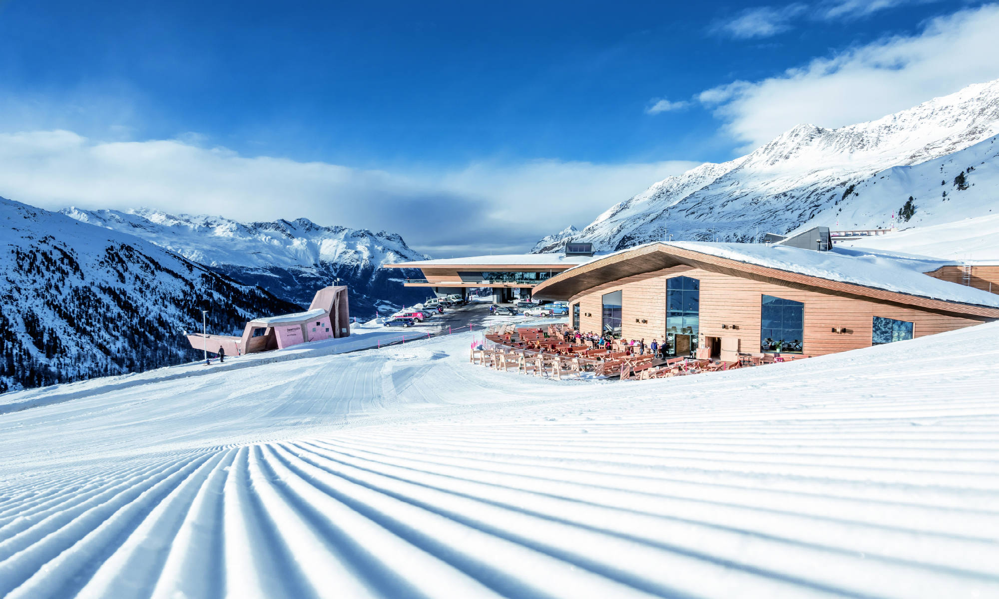 View of a mountaintop restaurant and the perfectly-groomed pistes of Obergurgl.