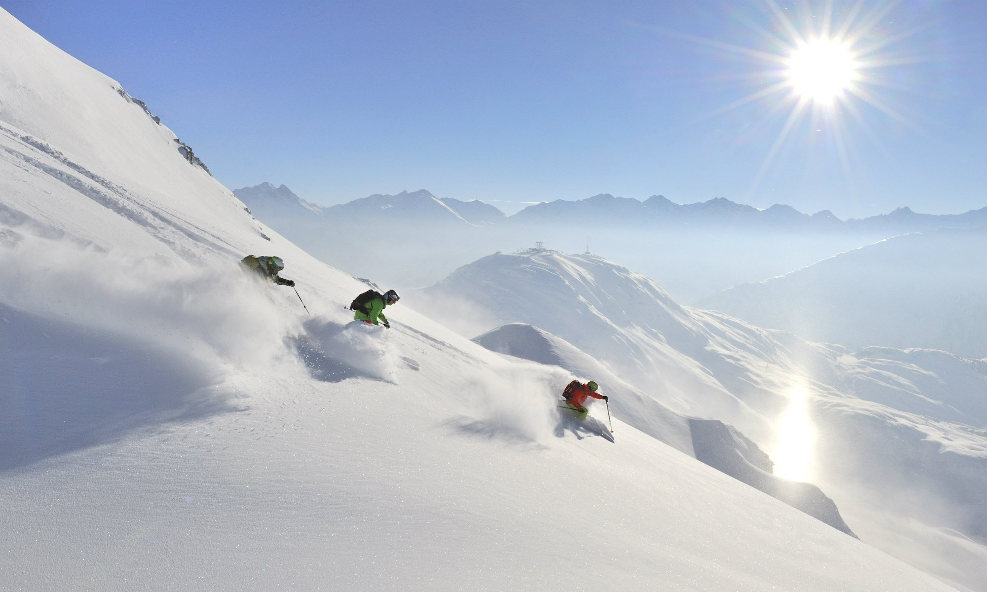 Three freestyle skiers on powder snow in St. Anton.