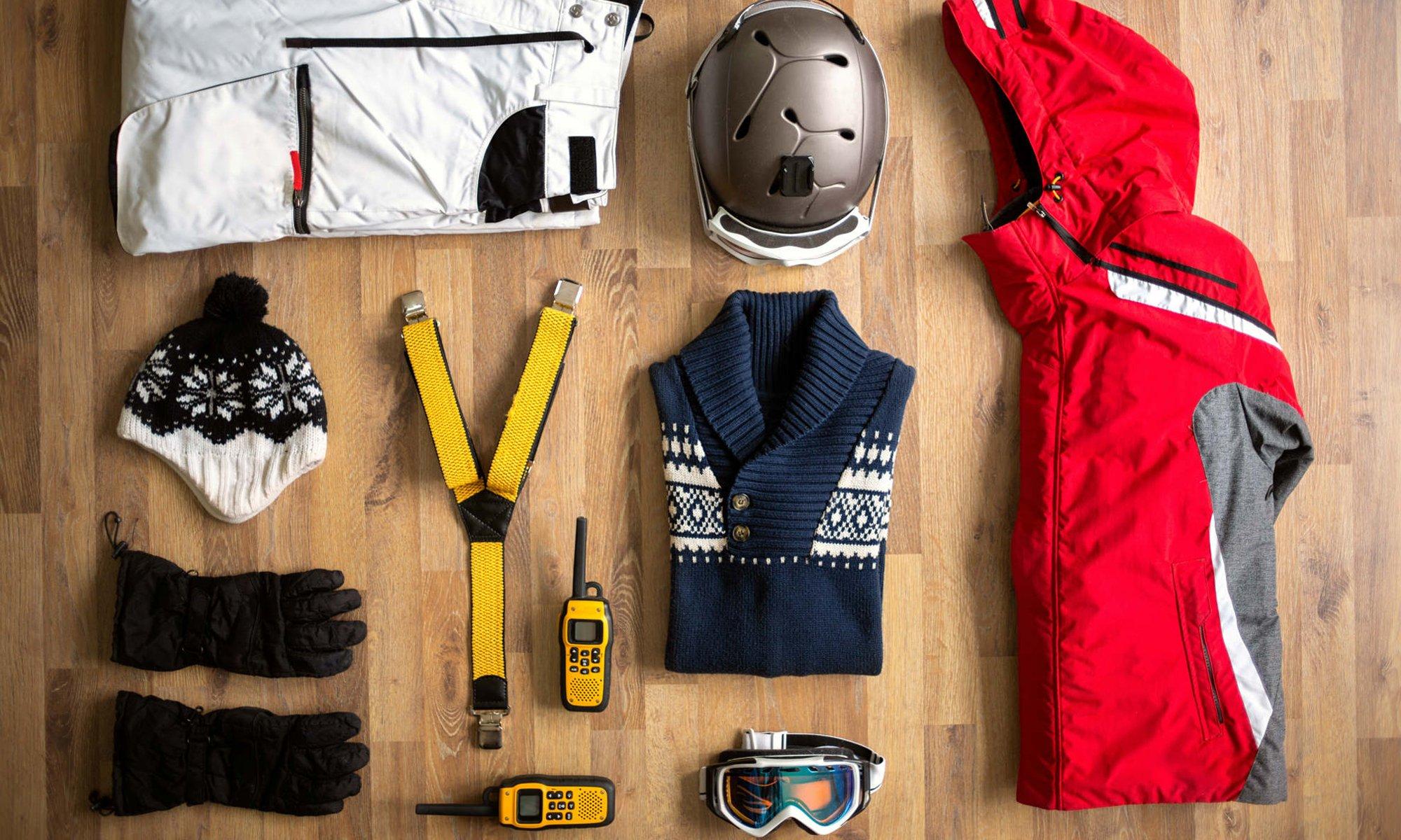 Een overzicht van alles wat je nodig hebt voor een perfecte dag op de piste zoals een skibroek en ski-jas, handschoenen, muts, skibril en een lekkere warme trui.