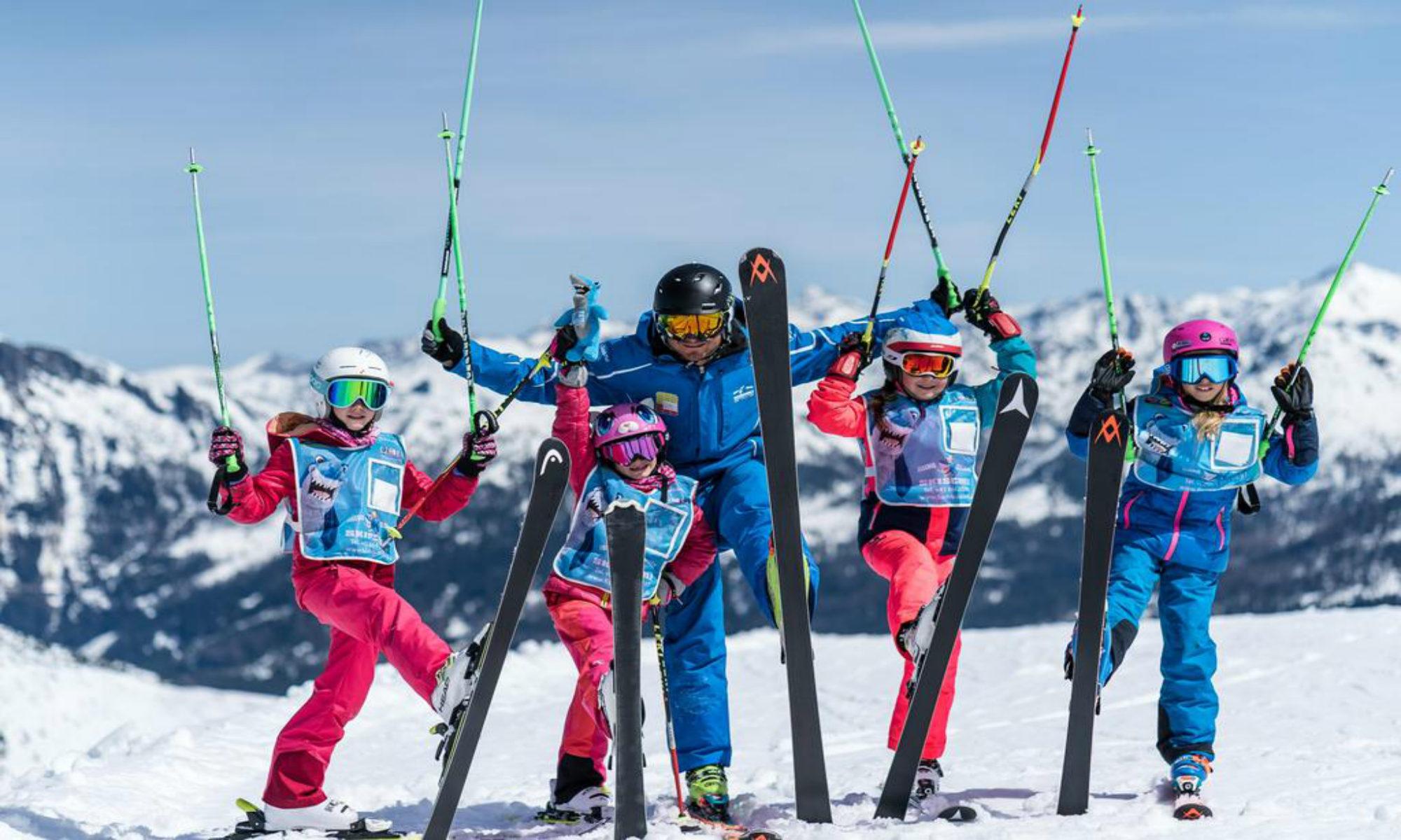 Een groepje leerlingen poseert voor een foto met hun skileraar in het skigebied van Flachau.