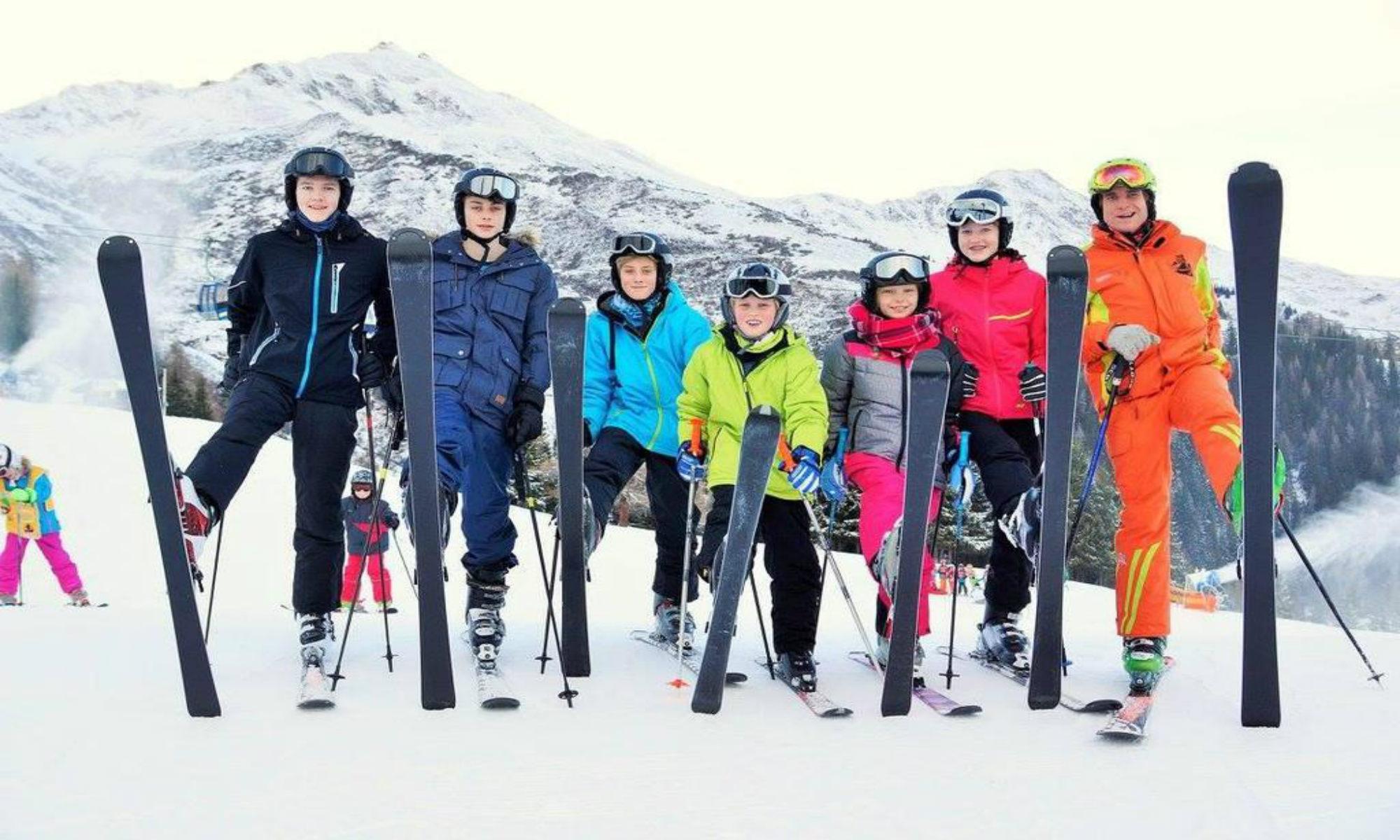 Een groep leerlingen poseert voor een foto met hun skileraar.