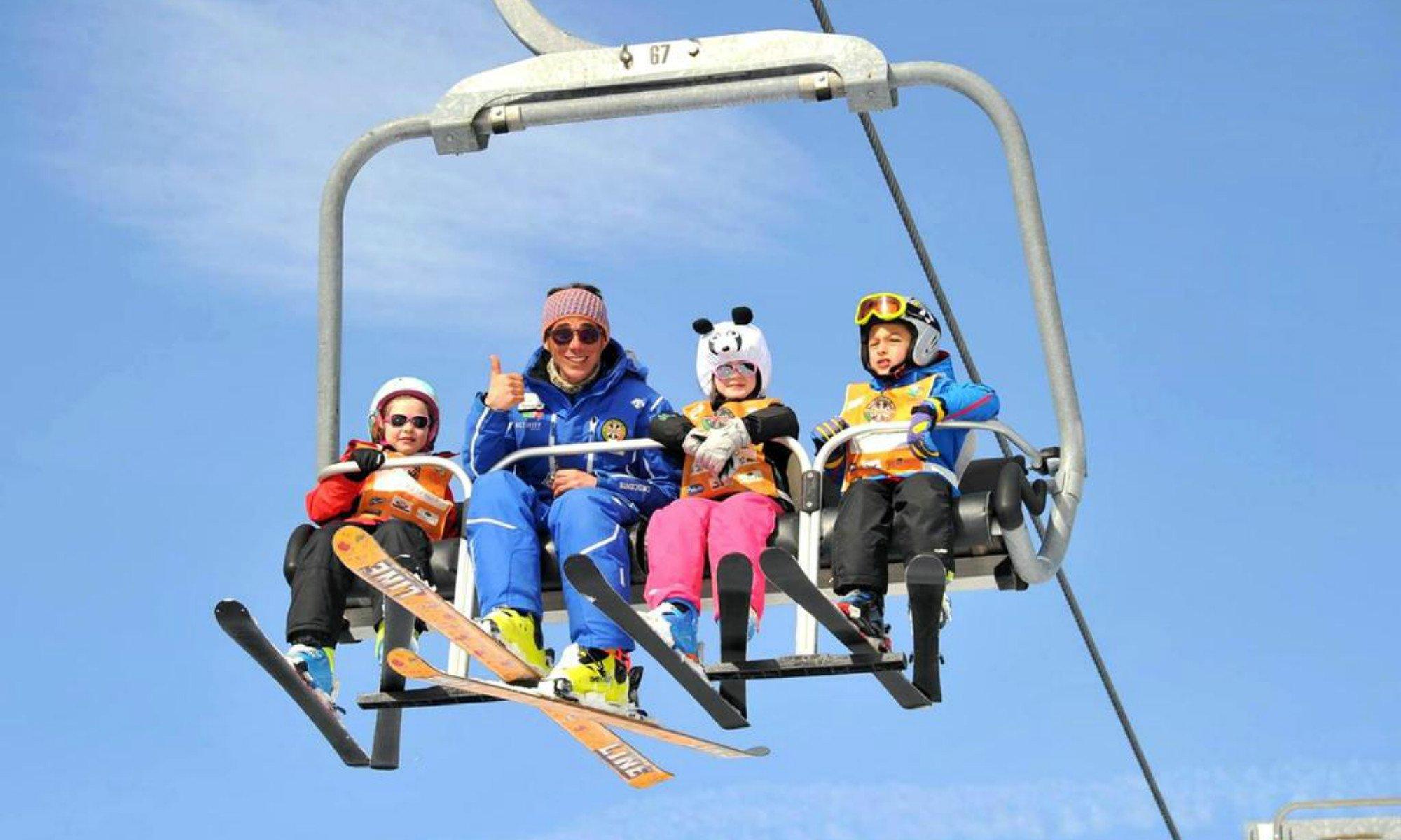 Un istruttore di sci e 3 piccoli allievi sorridono verso la macchina fotografica mentre sono sullo skilift.