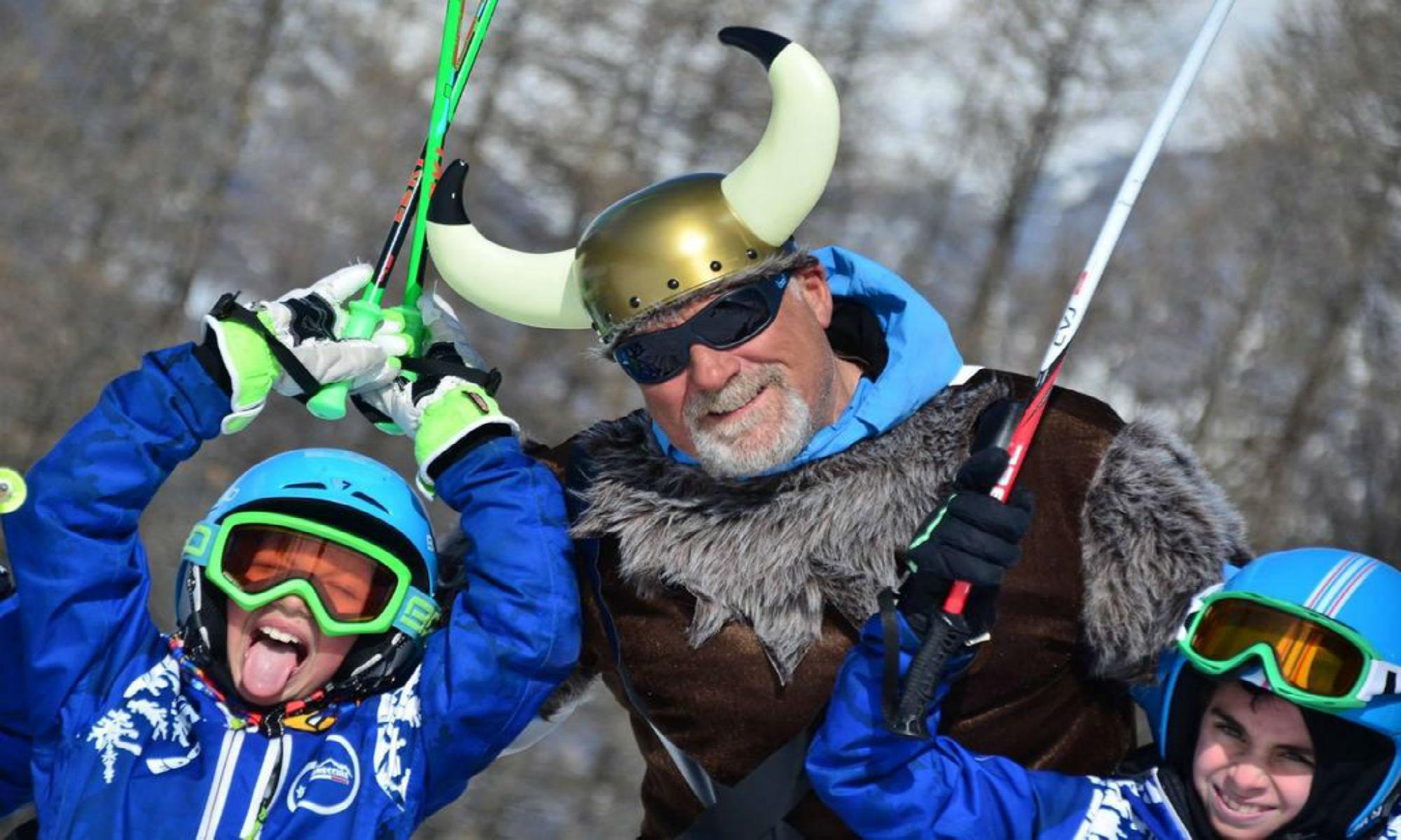 Un maestro di sci vestito da vichingo per Carnevale sorride verso l'obiettivo assieme a due piccoli allievi entusiasti.
