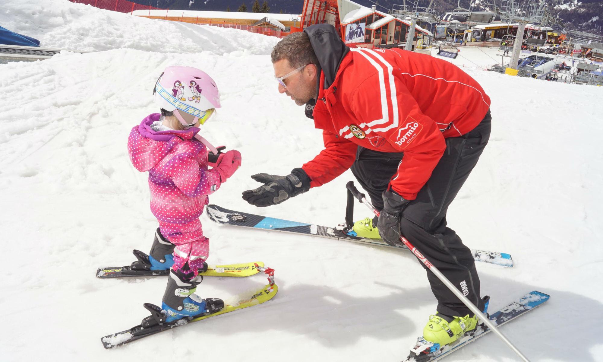 Un maestro di sci insegna la posizione dello spazzaneve a una piccola sciatrice.