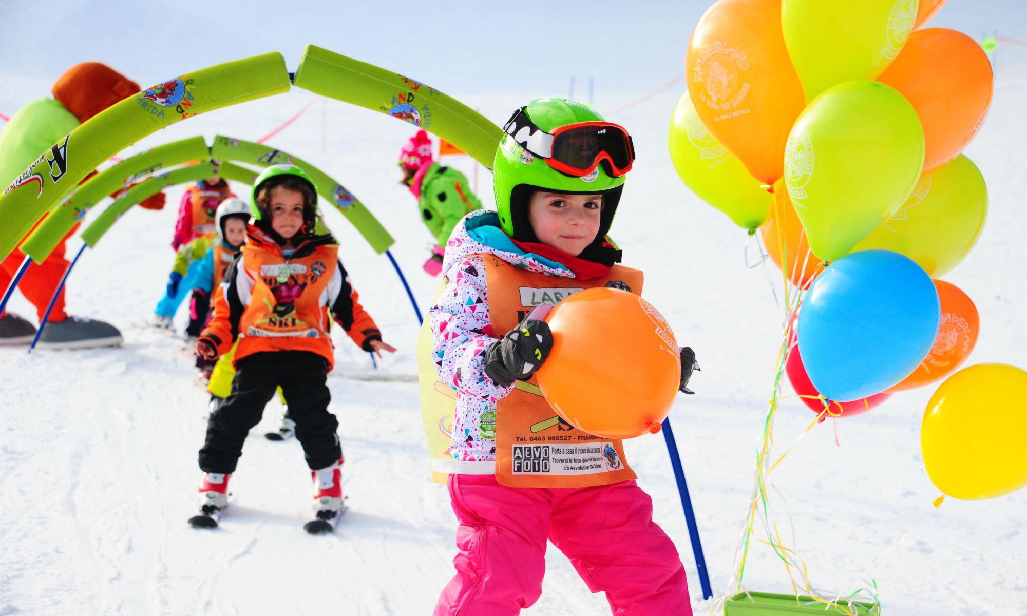 Un gruppo di bambini impara a scivolare sulla neve, attraversando un percorso colorato e trasportando palloncini.