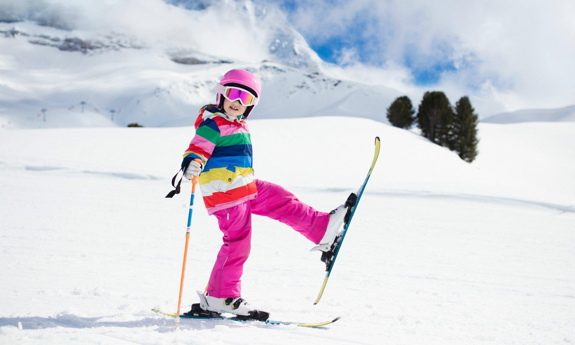 Una piccola sciatrice mostra gli sci ai piedi