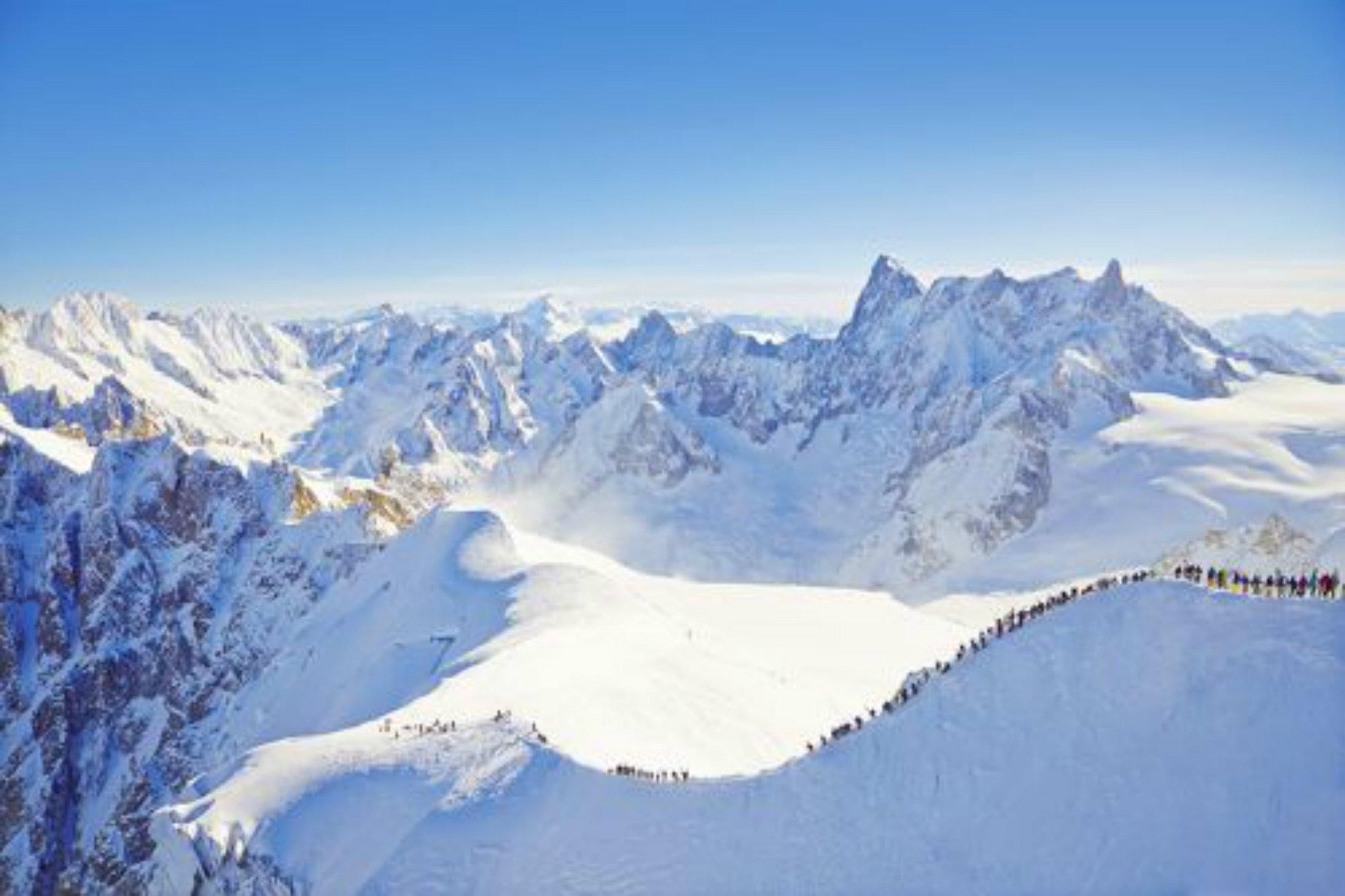 Des skieurs descendent la crête de l'Aiguille du Midi avant de se lancer dans la descente de la Vallée Blanche.