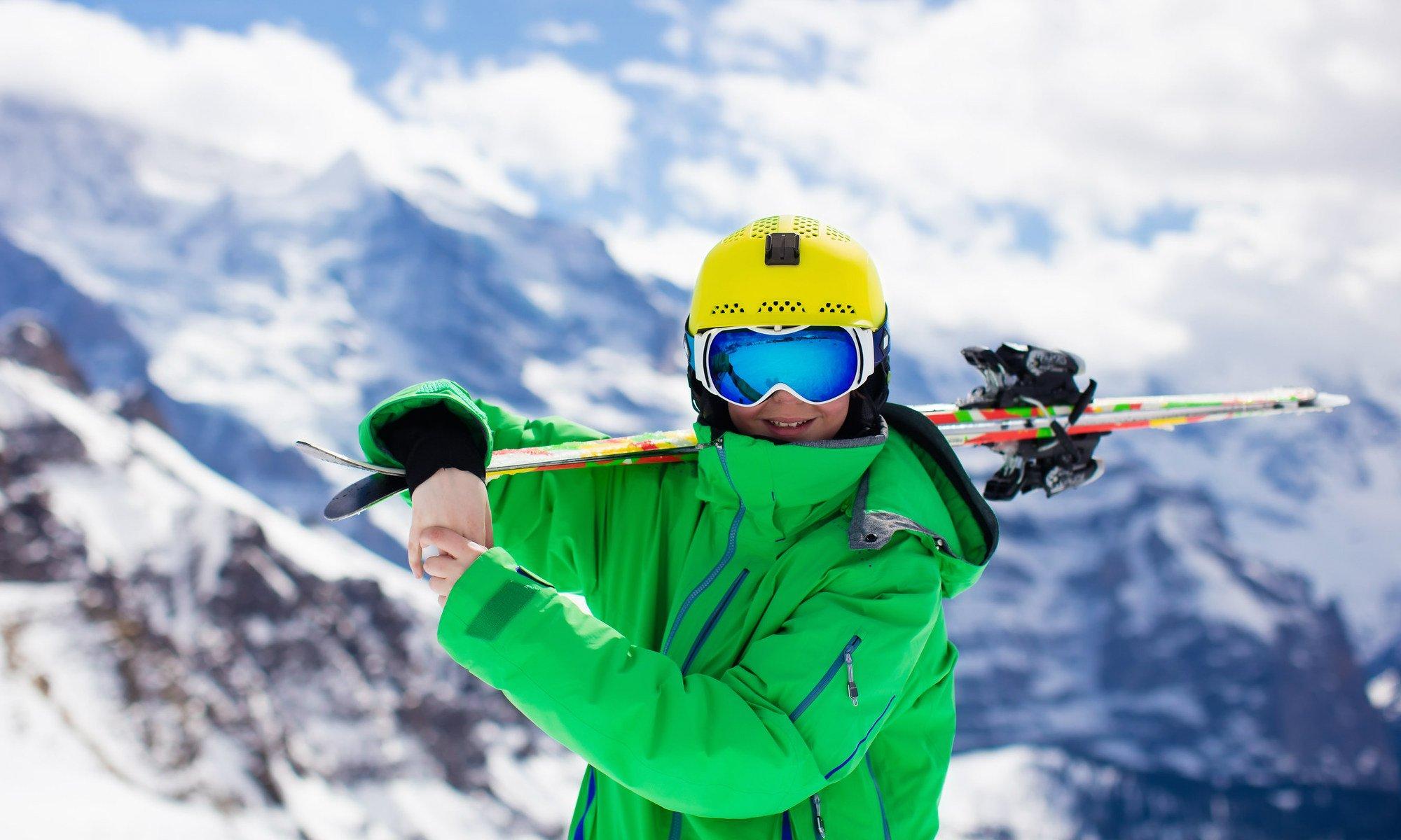 Un skieur souriant, skis sur les épaules.