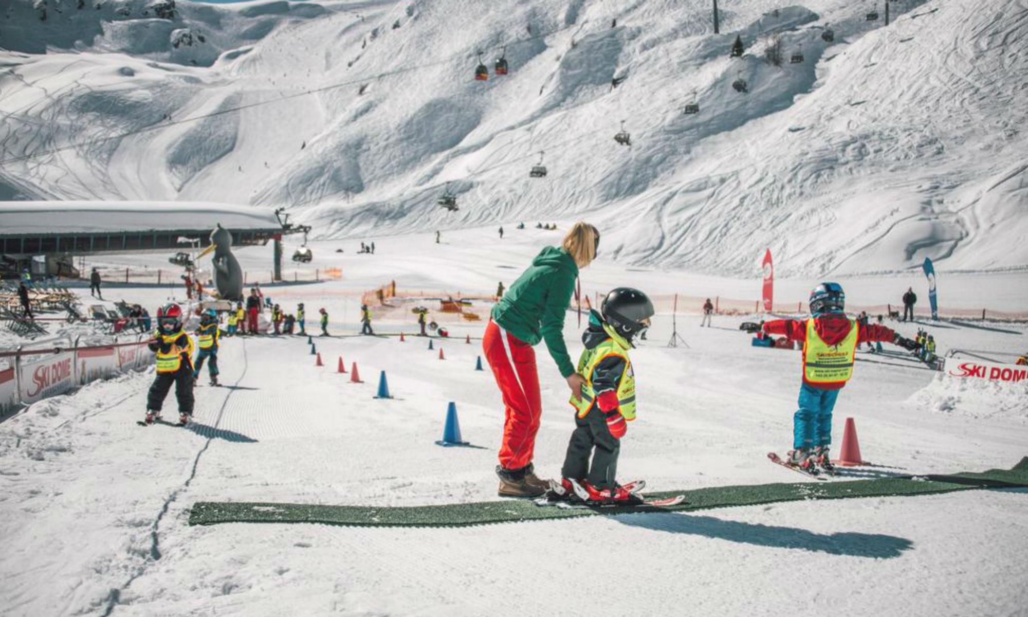 Twee kinderen oefenen het skiën onder het toeziend oog van hun skilerares in het skigebied van Kaprun.