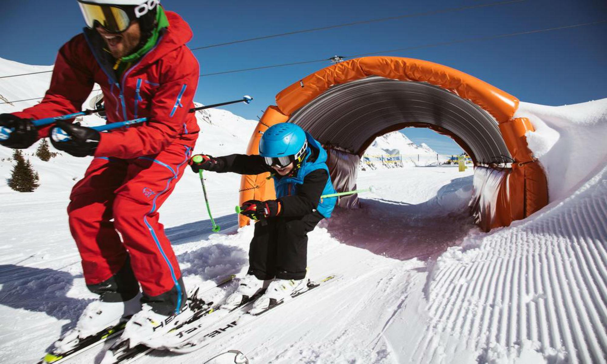 Een jonge skiër en zijn skileraar hebben veel plezier tijdens een privéles in Lech.