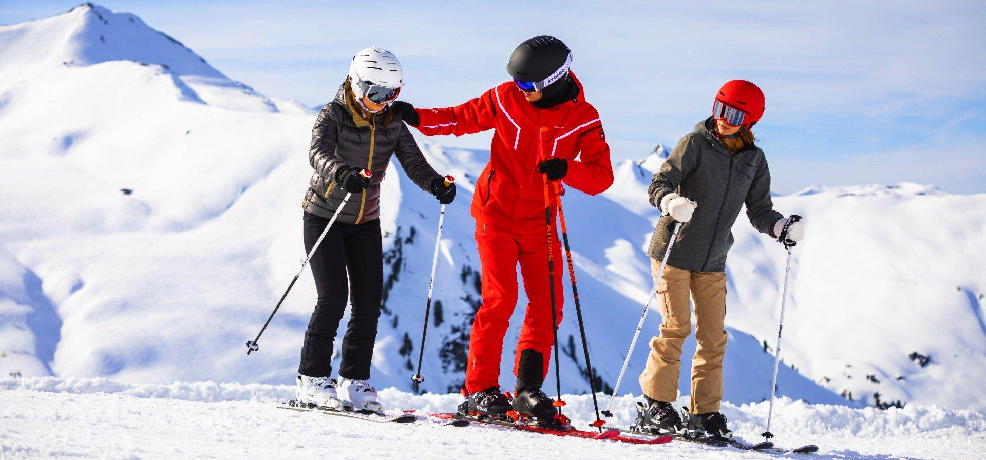 Een skileraar leert twee meisjes skiën.