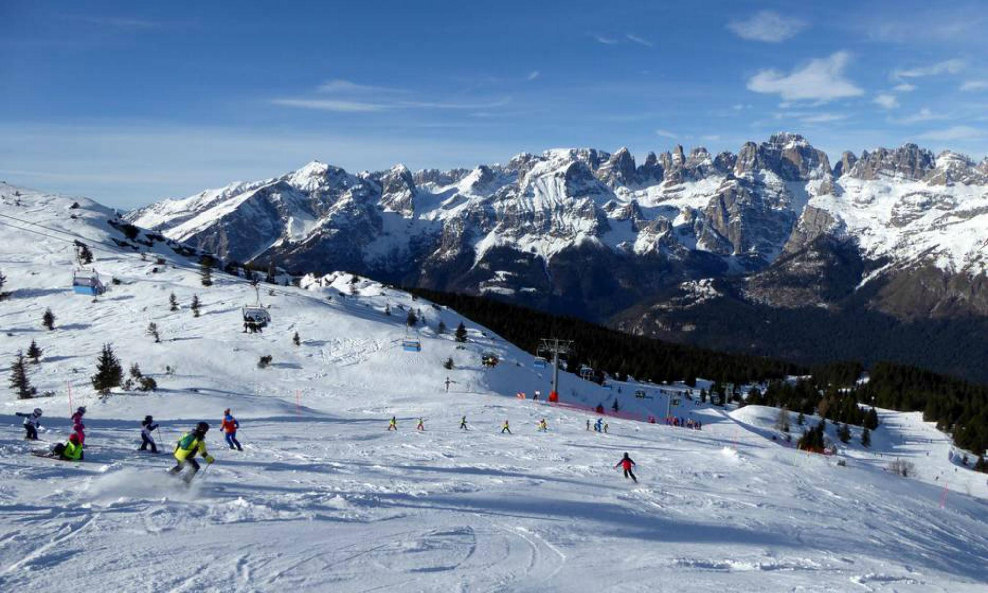 Vista dalla Cima Paganella con numerosi sciatori che scivolano lungo il pendio innevato.