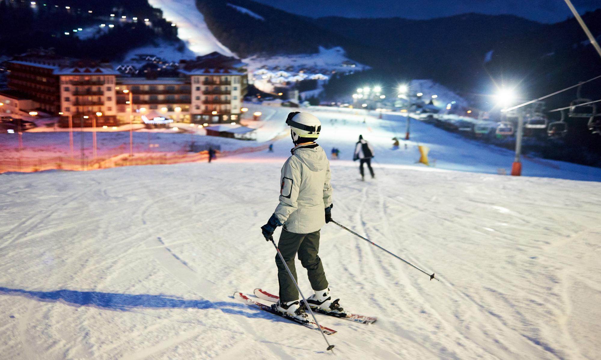 Uno sciatore in procinto di cominciare la discesa di una pista illuminata di notte.
