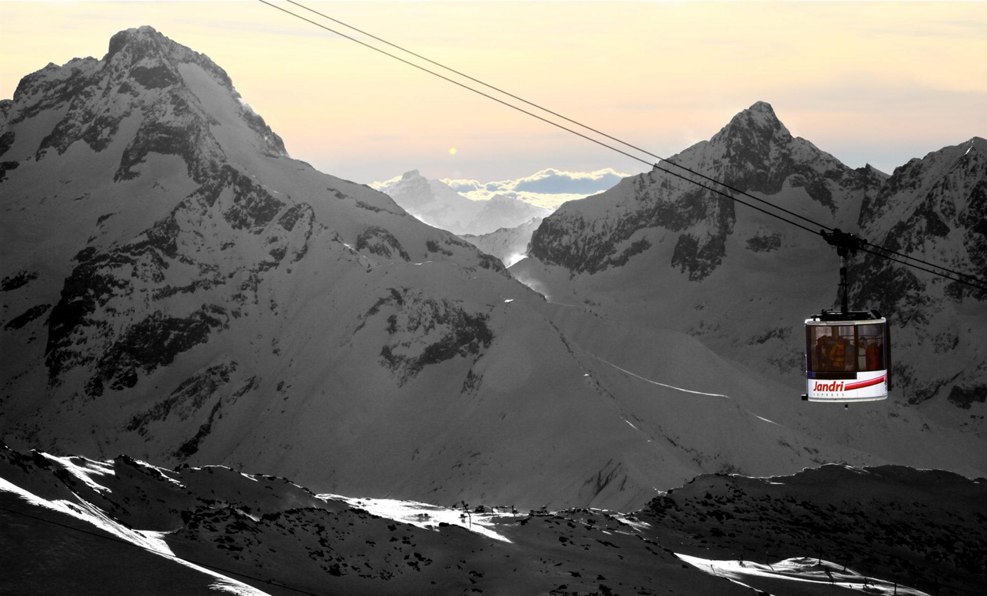 Vue sur la télécabine Jandri aux Deux Alpes, devant des sommets enneigés et un magnifique soleil couchant.