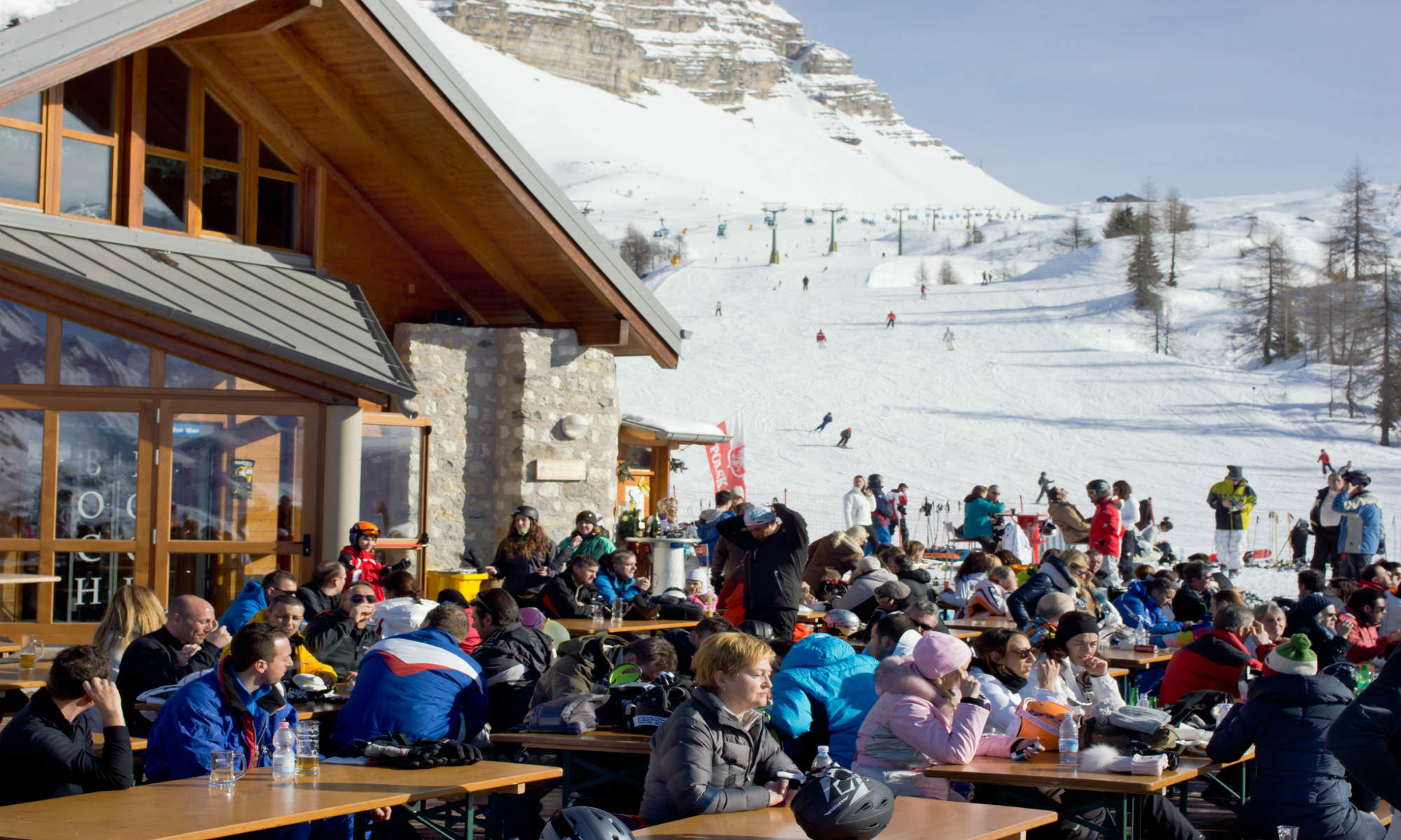 Skiers on a piste and others enjoying a rest in the sunshine at Madonna di Campiglio.