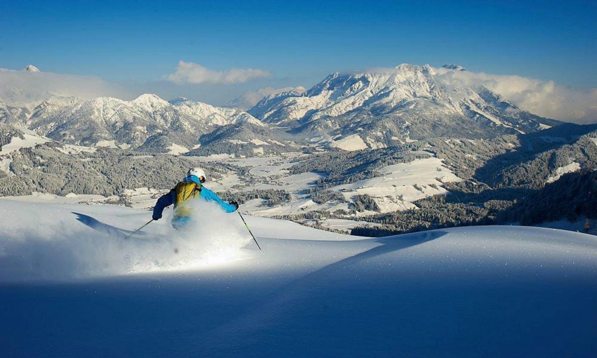 Een skiër geniet van de verse sneeuw in het skigebied van Fieberbrunn.
