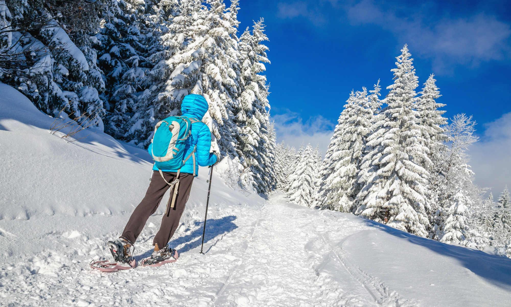 Een vrouw maakt een sneeuwschoenwandeling in een prachtig besneeuwd landschap.