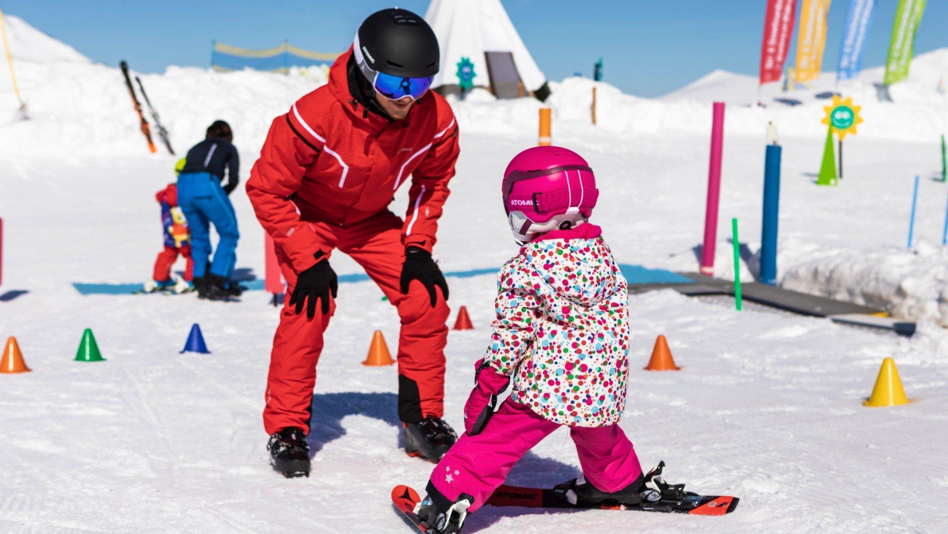 Ein Skilehrer gibt einem kleinen Mädchen Skiunterricht.