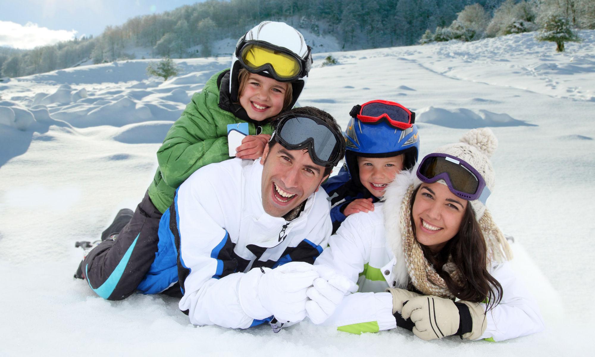 Una famiglia, composta da mamma, papà e due figli, posa sulla neve, sorridendo verso la macchina fotografica.