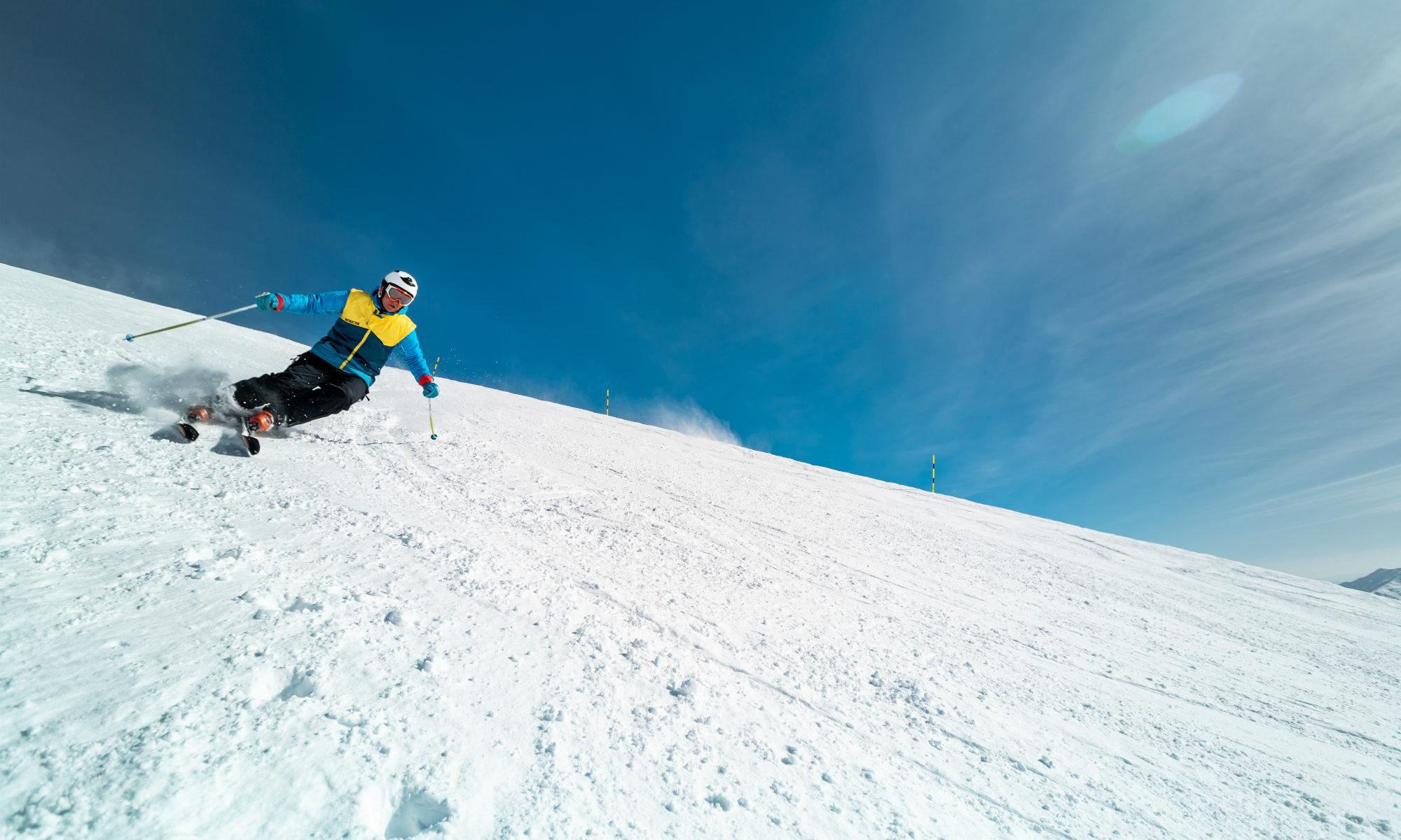 Un abile sciatore dimostra la sua tecnica sulla neve lungo un pendio particolarmente difficile.