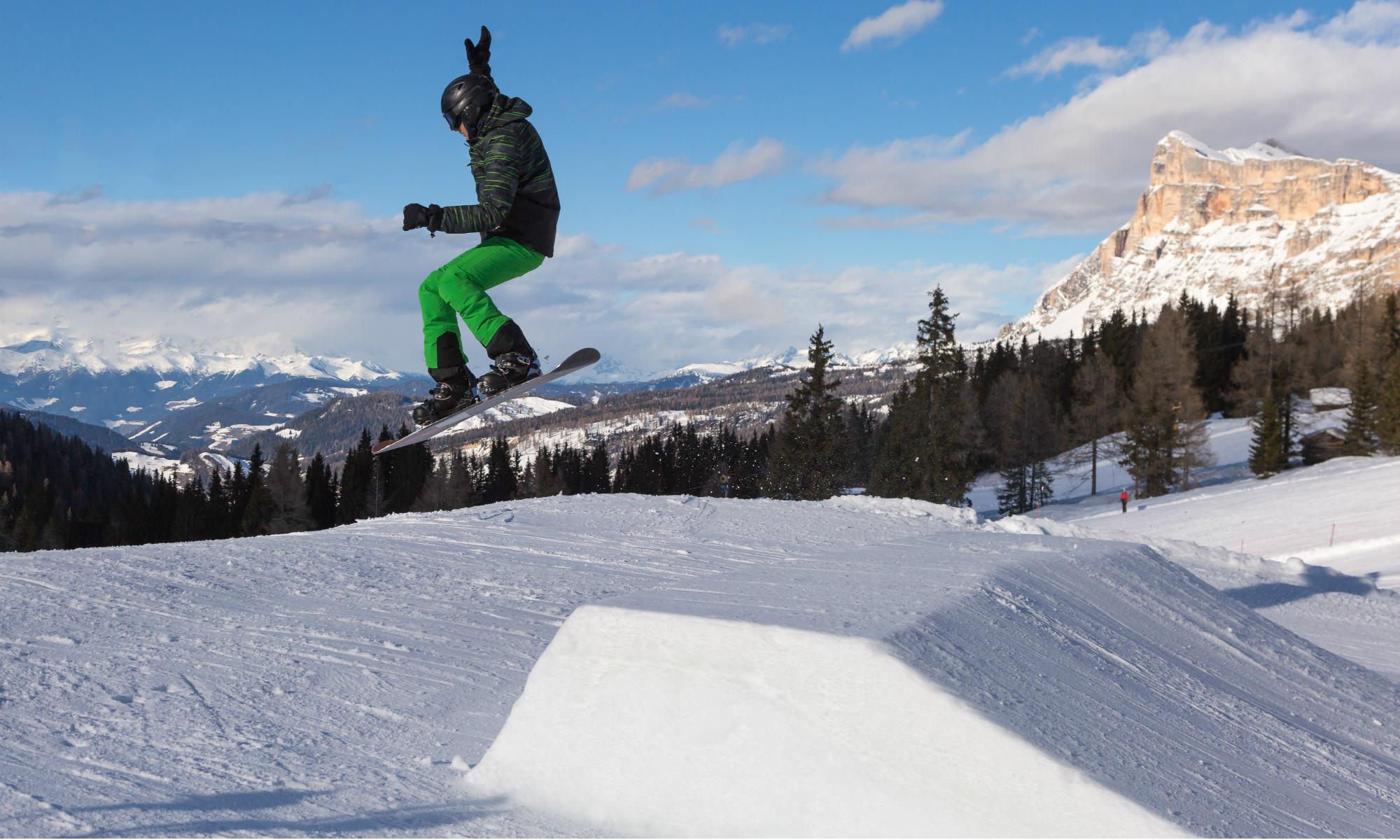Uno snowboarder utilizza l'aiuto di un jump per fare acrobazie sulla tavola.