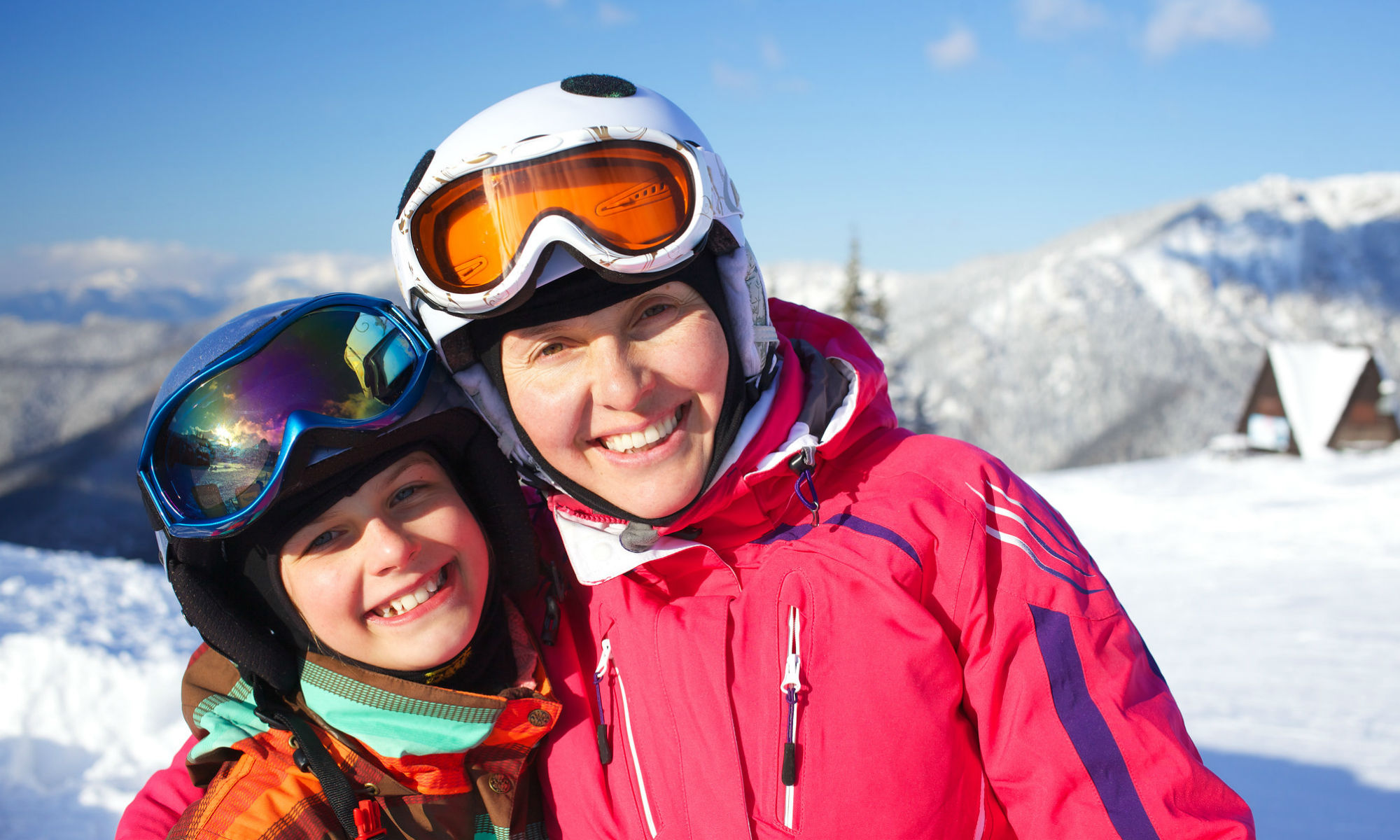 Une mère et sa fille adolescente posent tout sourire sur les pistes enneigées.