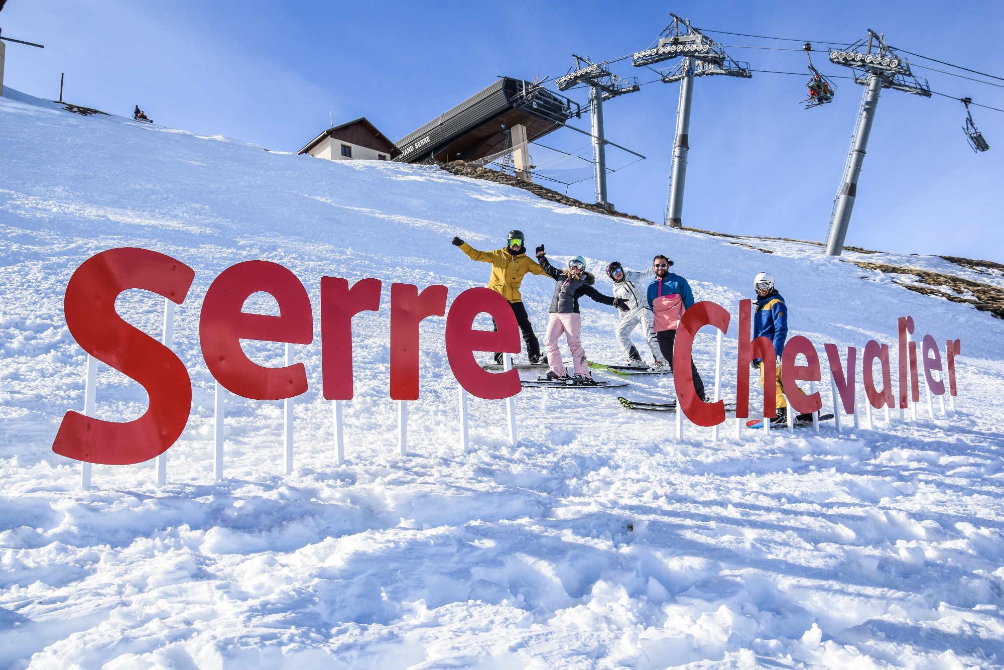 Un groupe d'amis pose dans la neige derrière les grandes lettres Serre Chevalier.