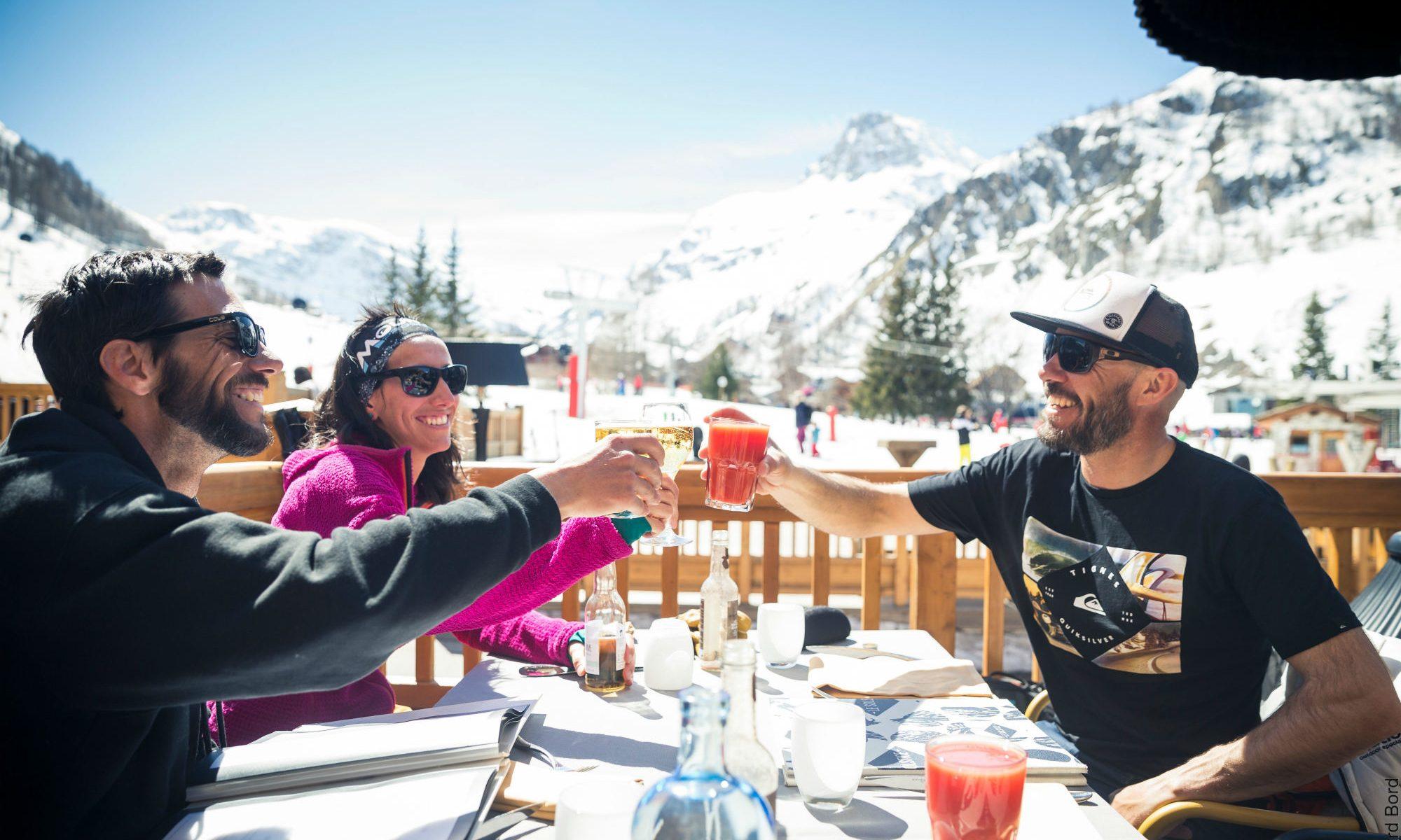 Trois amis trinquent à la terrasse ensoleillée d'un restaurant d'altitude à Val d'Isère.
