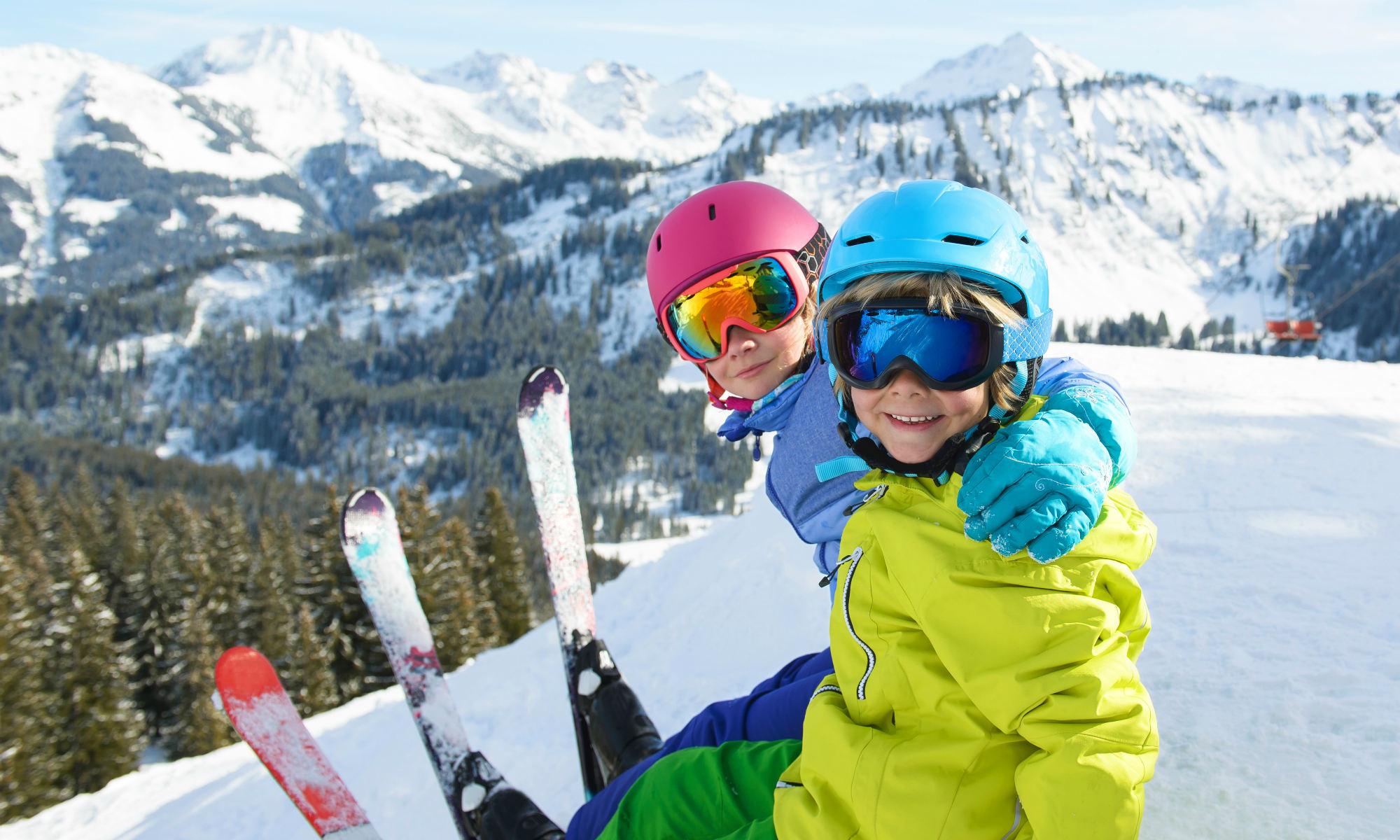 Un frère et une soeur souriants sont assis dans la neige en haut d'une piste de ski.