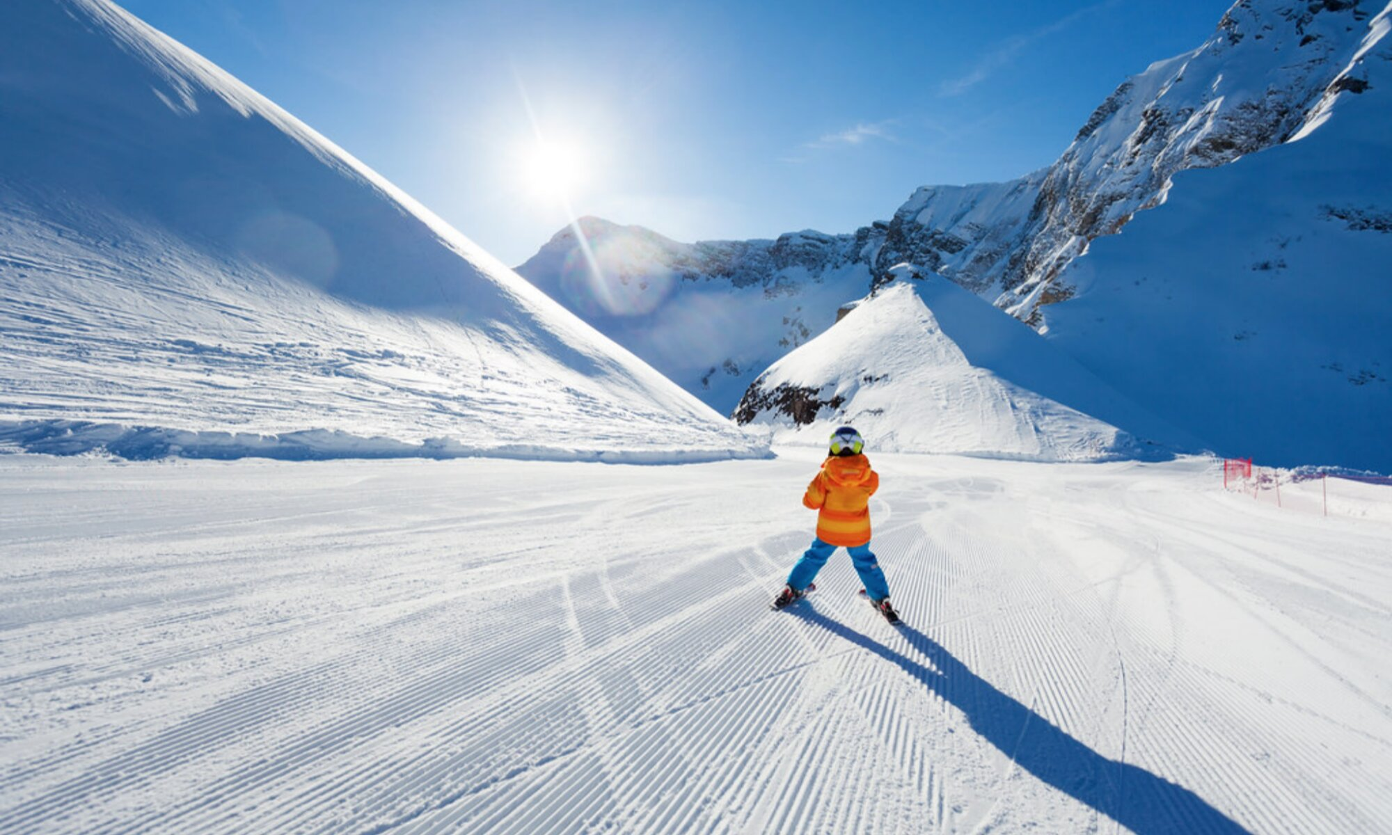A young skier on a well-groomed beginner slope in Cortina d'Ampezzo.