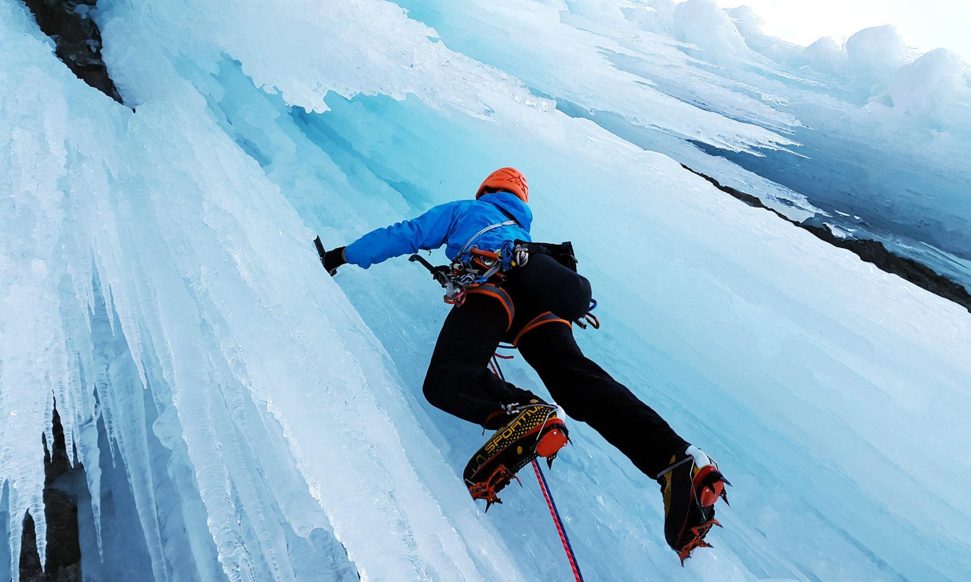 Een ijsklimmer beklimt een bevroren waterval.