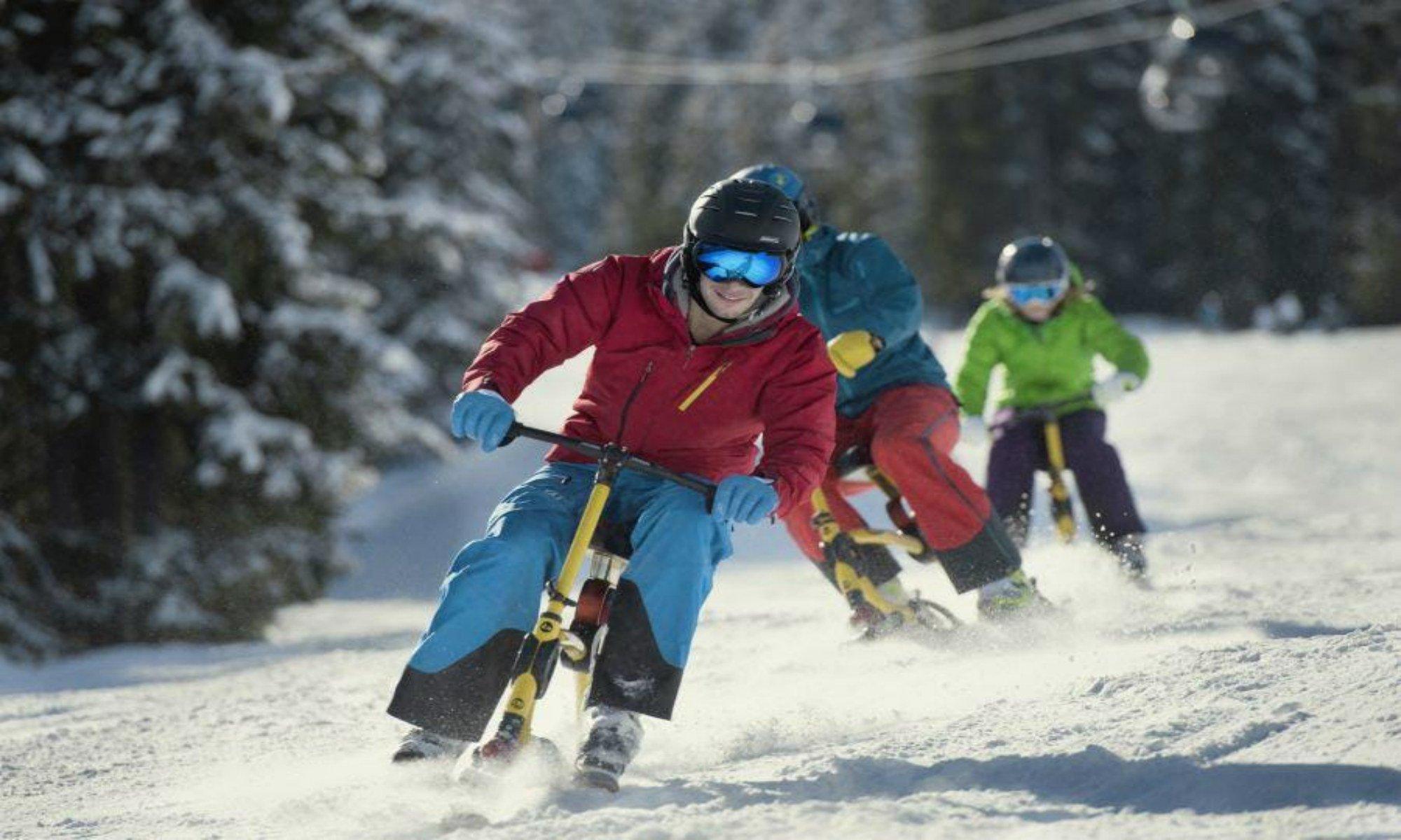 Drie snowbikers dalen af van de piste in het skigebied van Flachau.